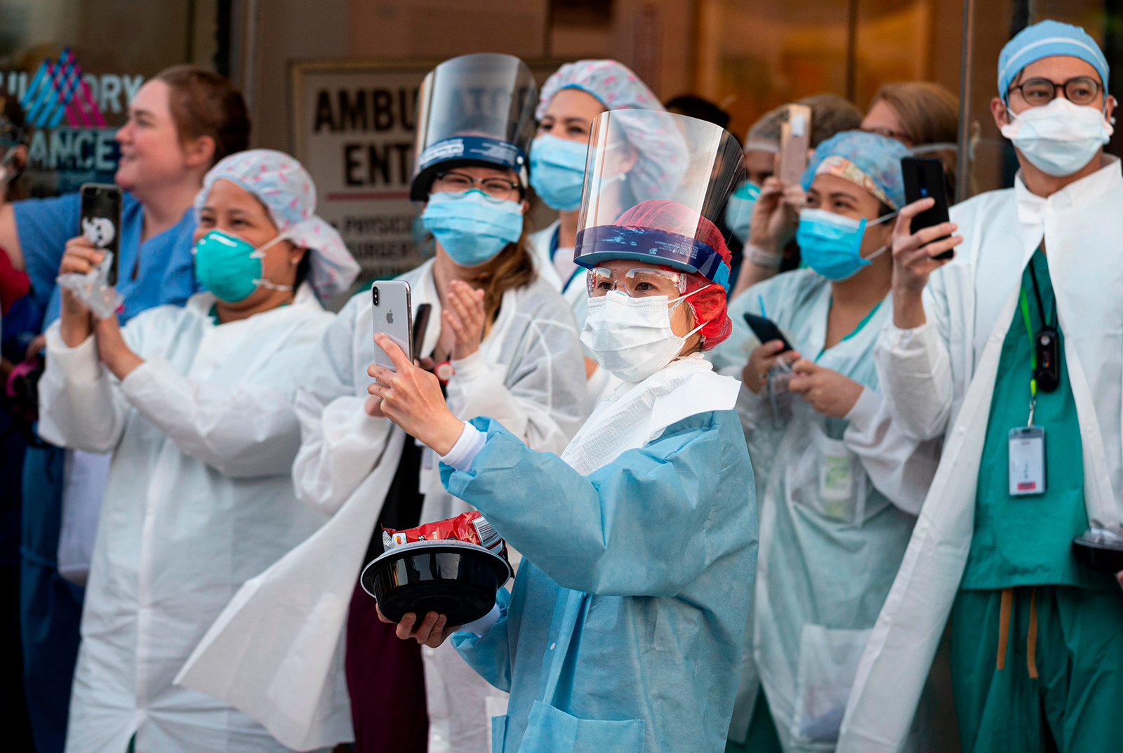 Healthcare workers react to people applauding in front of the Mount Sinai Hospital in Queens to show gratitude to medical staff and essential workers on the front lines of the coronavirus pandemic, on Wednesday, April 15.