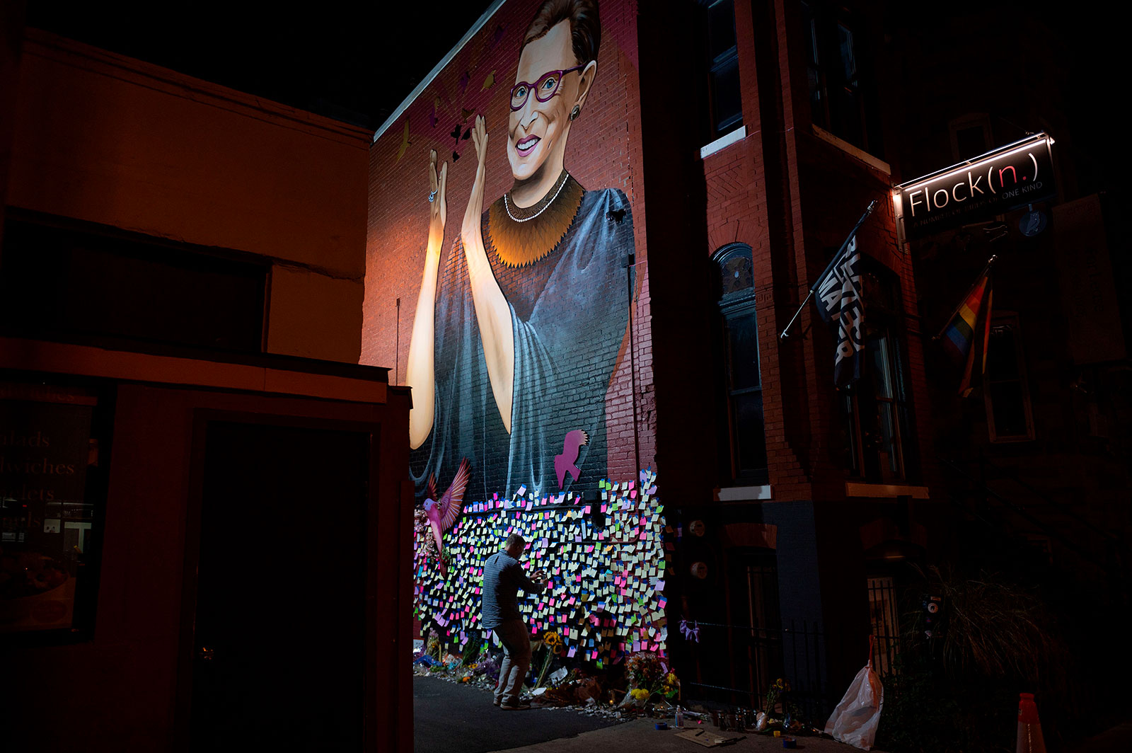Andrew Oros takes photos of notes left at a mural for Justice Ruth Bader Ginsburg in downtown Washington, DC