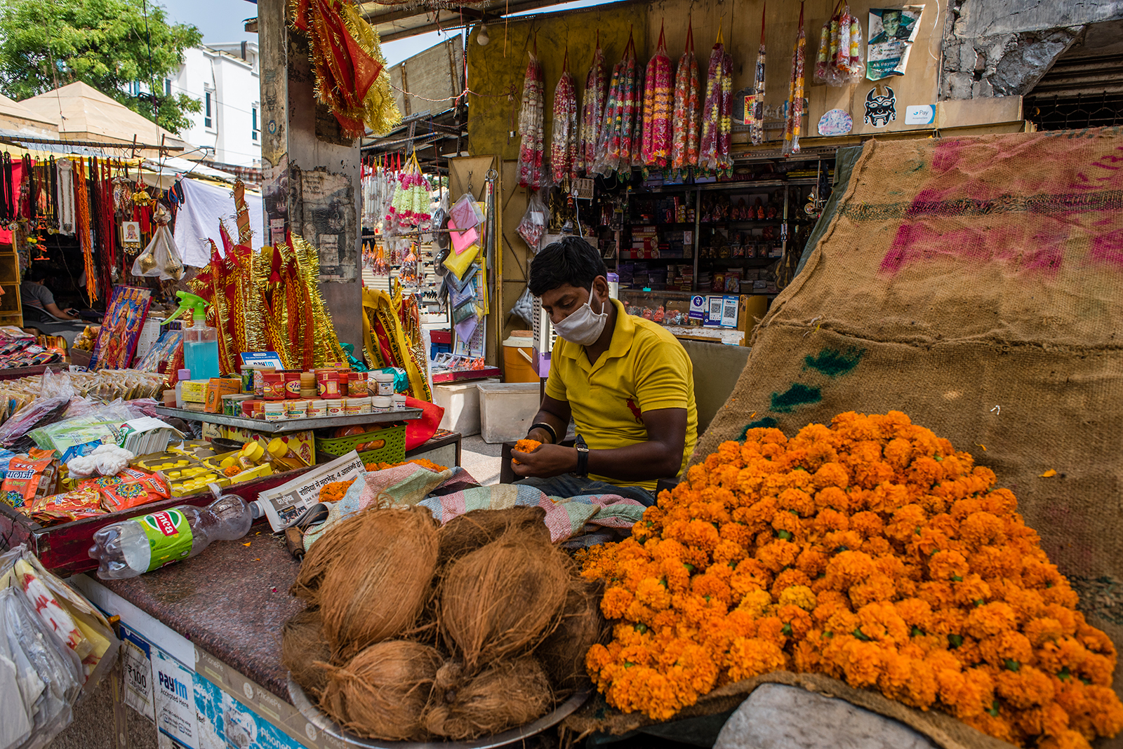 An Indian shopkeeper sells votive threads, coconuts and flower garlands on June 8, in Delhi, India.