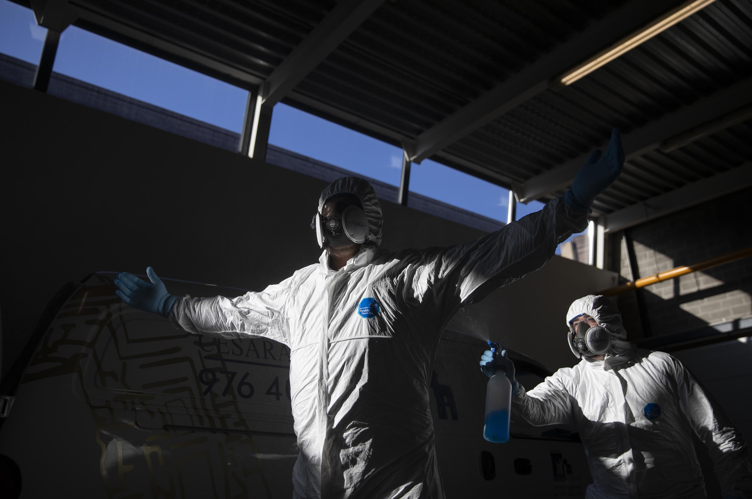 Cemetery workers disinfect each other after moving the body of a coronavirus victim at the Torrero de Zaragoza crematorium on April 13, in Zaragoza, Spain.