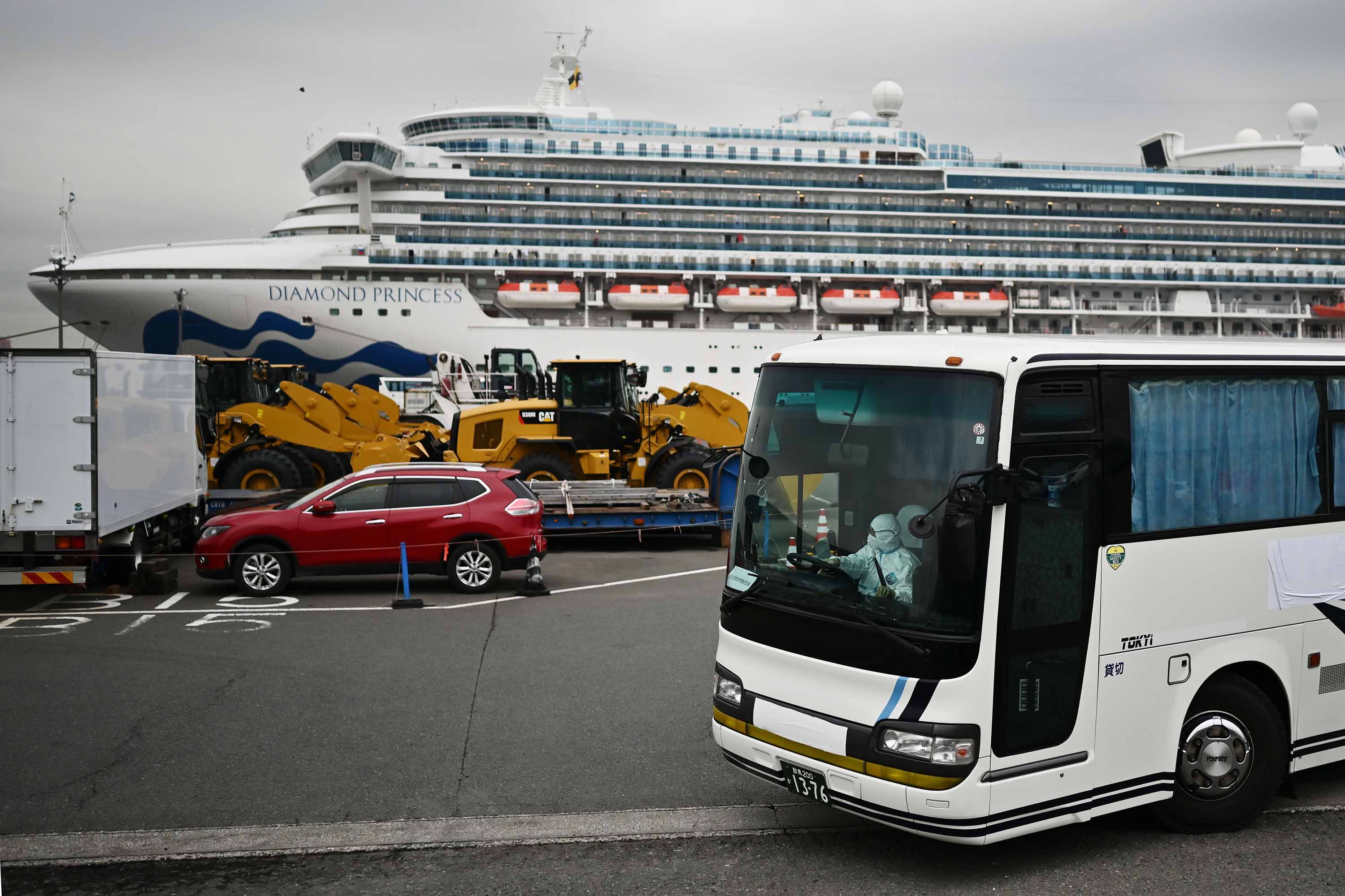 A bus with a driver wearing full protective gear departs from the port where the Diamond Princess cruise shipis docked in Yokohama, Japan, on Friday.