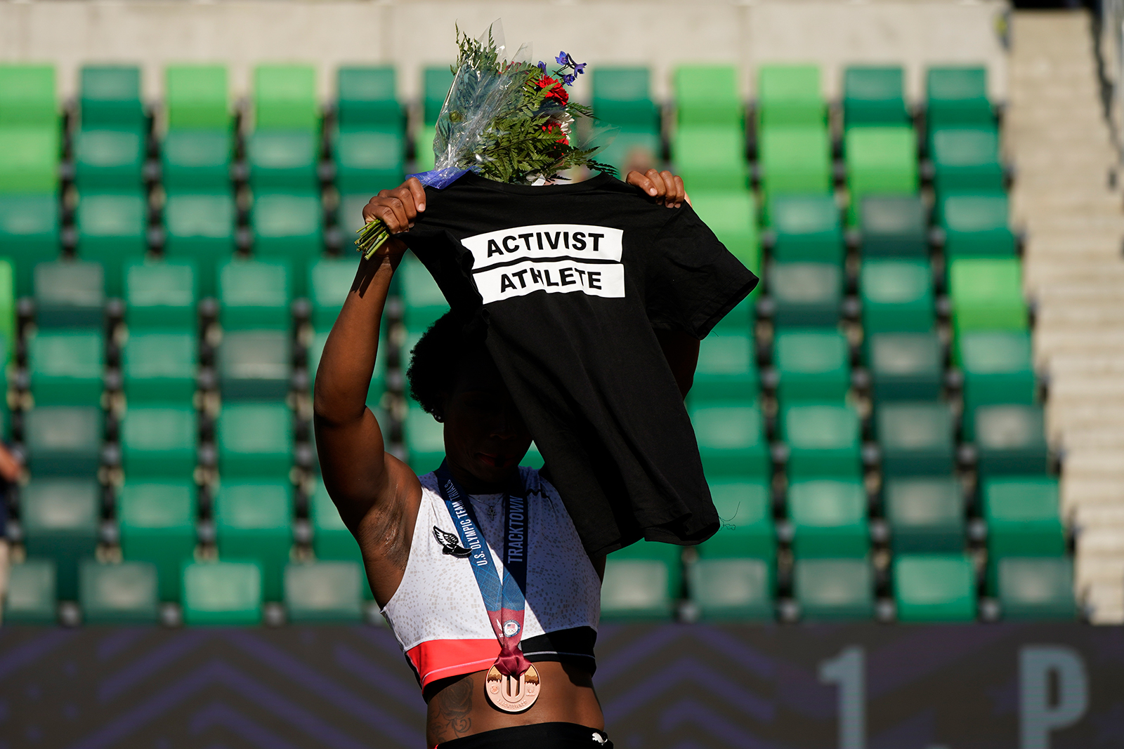 Gwendolyn Berry holds her Activist Athlete T-shirt over her head during the metal ceremony at the US Olympic Track and Field Trials on June 26, in Eugene, Oregon.