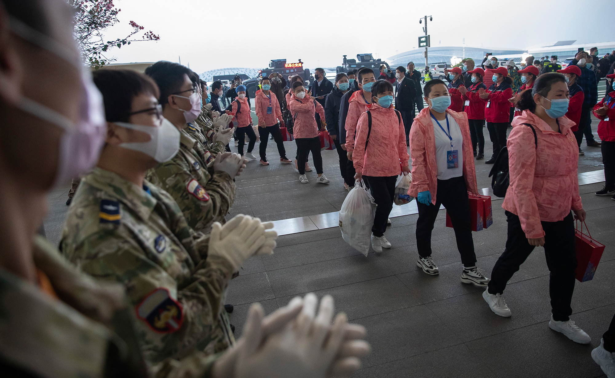 In this March 18 photo released by China's Xinhua News Agency, people applaud as departing medical workers enter Wuhan Tianhe International Airport in Wuhan in central China's Hubei Province.