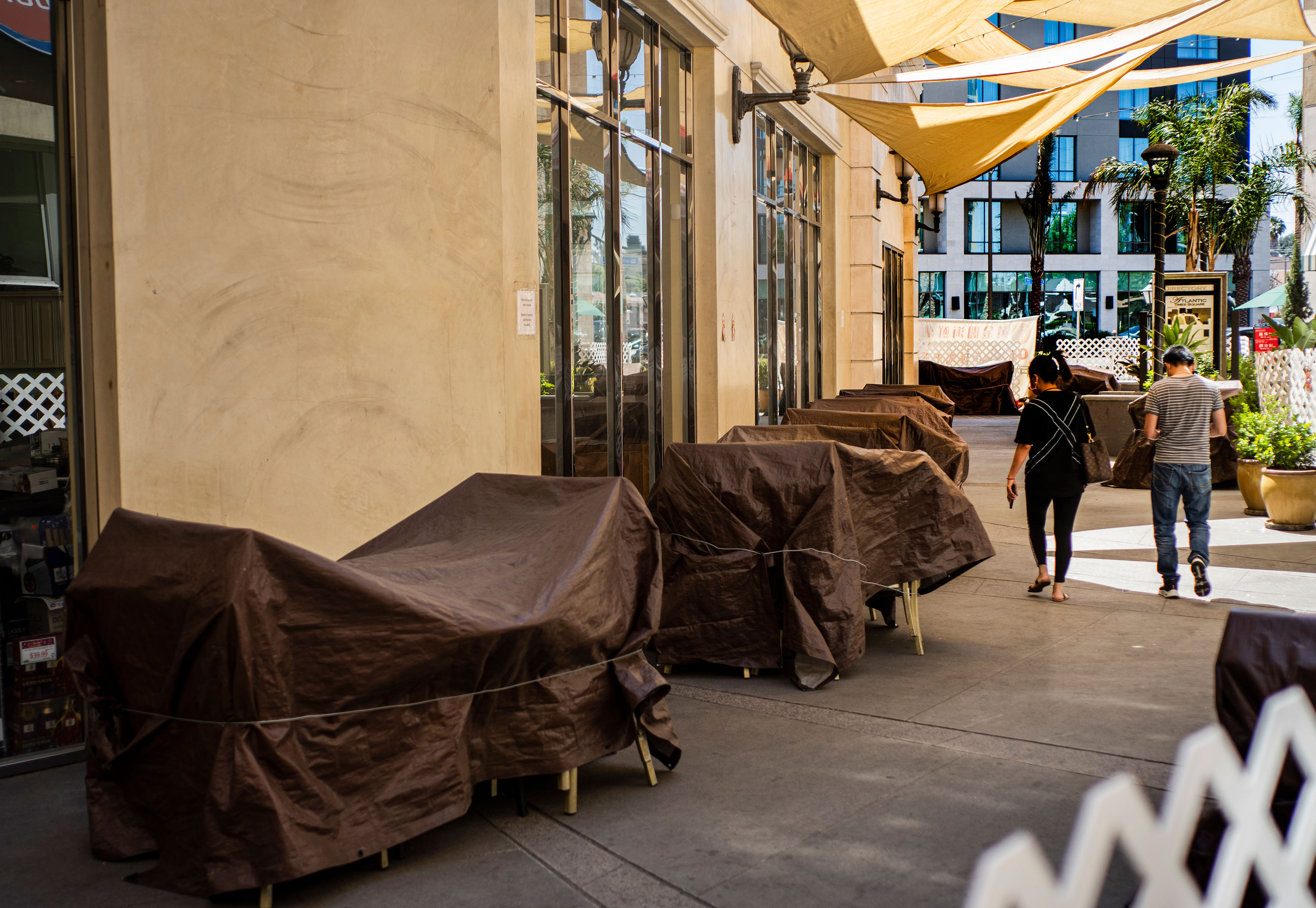 Restaurant chairs and tables remain covered at an outdoor mall in Los Angeles on Friday, June 11.