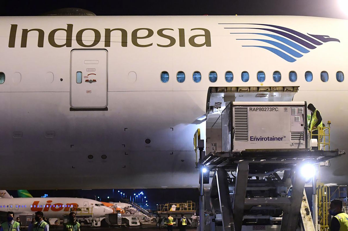 This handout photo taken on Dec. 6 and released by the Indonesian Presidential Palace shows workers unloading Sinovac Covid-19 vaccines at Jakarta International Airport, Indonesia.