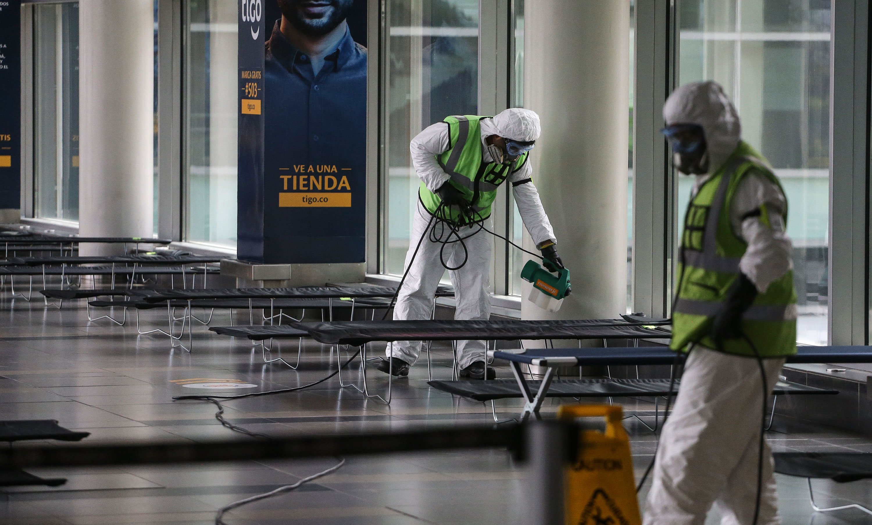 Airport employees disinfect the El Dorado International Airport, in Bogota, Colombia, on March 21.