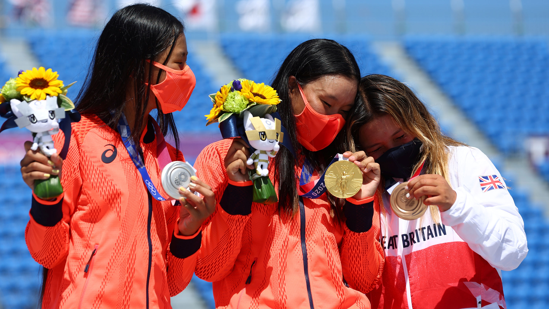 Gold medalist Sakura Yosozumi of Japan celebrates on the podium next to silver medalist Kokona Hiraki of Japan and bronze medalist Sky Brown of Great Britain after their park skateboarding final event on August 4.