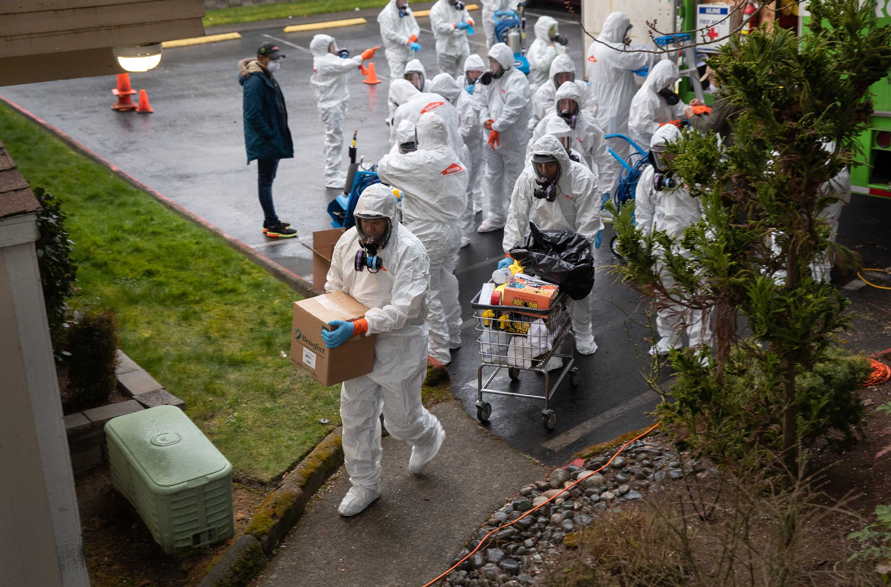 A cleaning crew takes disinfecting equipment into the Life Care Center on March 12, in Kirkland, Washington, where coronavirus deaths have been reported.