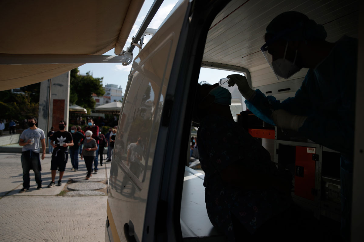 A medical worker collects a swab from a commuter during rapid tests for COVID-19 at a suburb in Athens, on October 22.