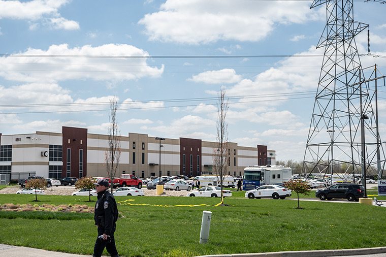 A police officer walks on the sidewalk near the crime scene in the parking lot of a FedEx Ground facility on April 16, in Indianapolis, Indiana.
