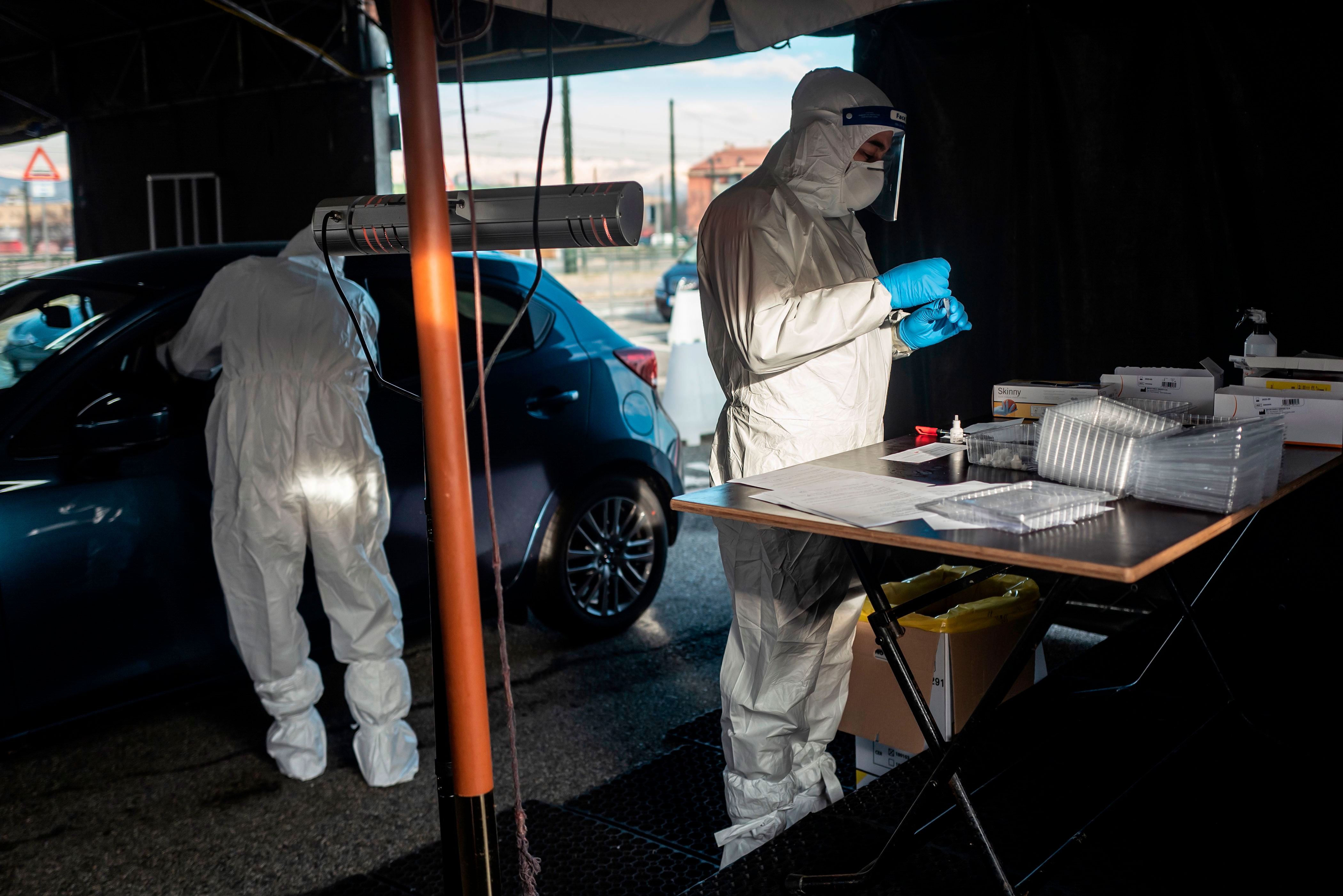 Military medical workers collect swab samples at a drive-thru Covid-19 testing center in Turin, Italy, on January 12.