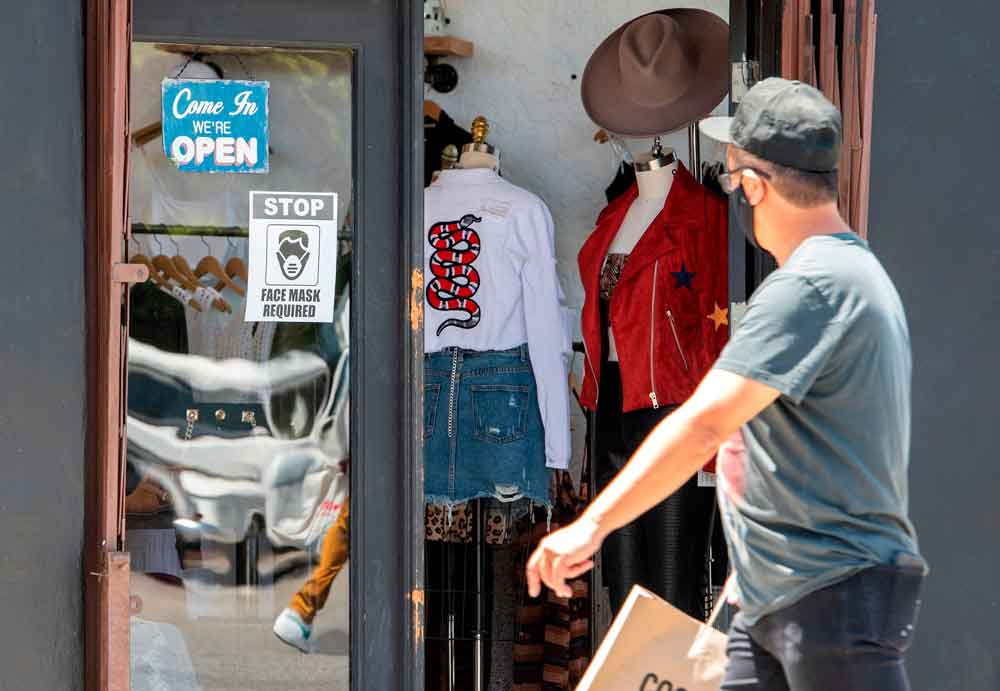 A man walks by a store requiring shoppers to wear face masks on May 27 in Los Angeles.
