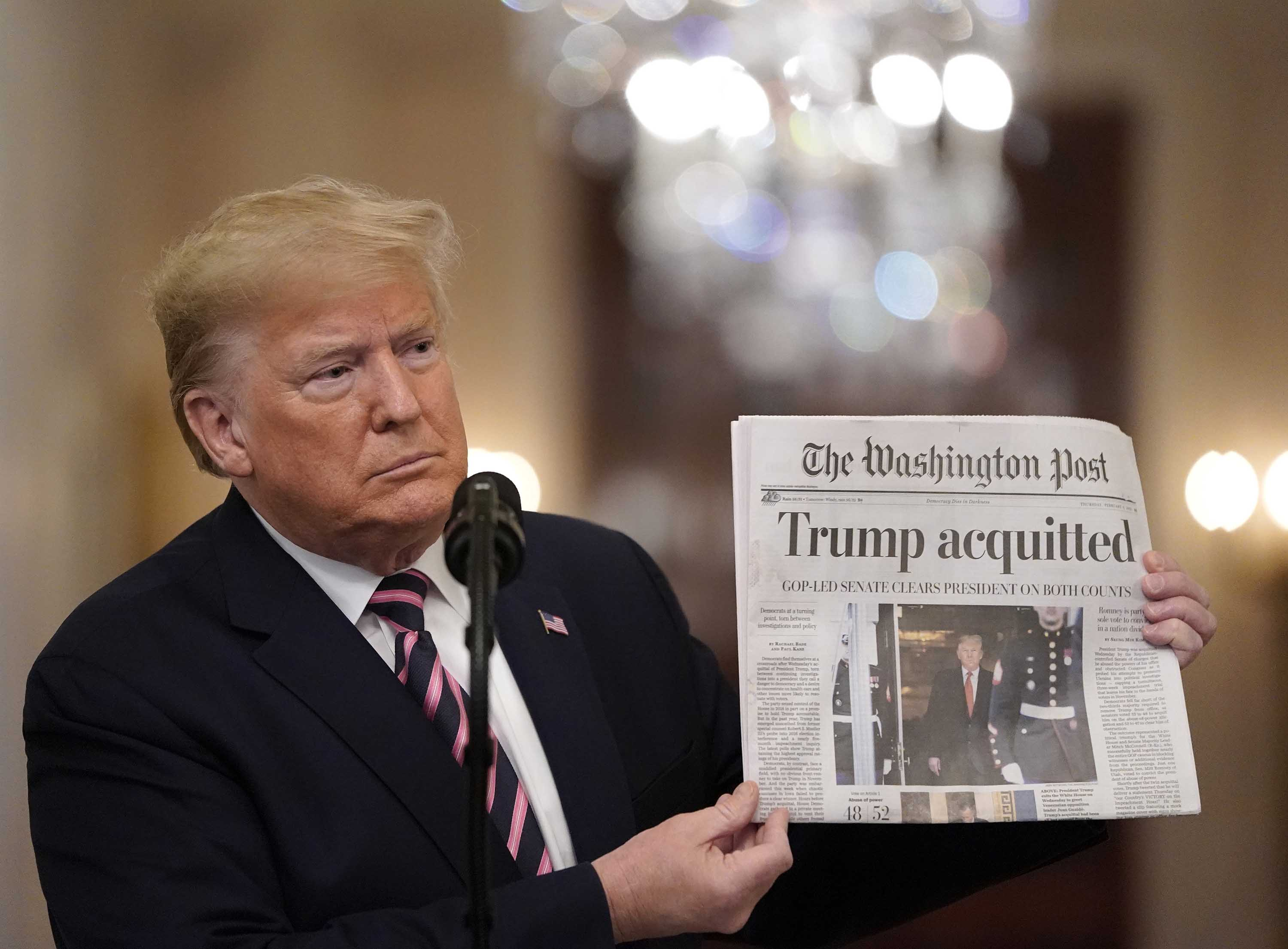 President Donald Trump holds a copy of The Washington Post as he speaks in the White House, one day after the U.S. Senate acquitted on two articles of impeachment, on February 6, 2020.