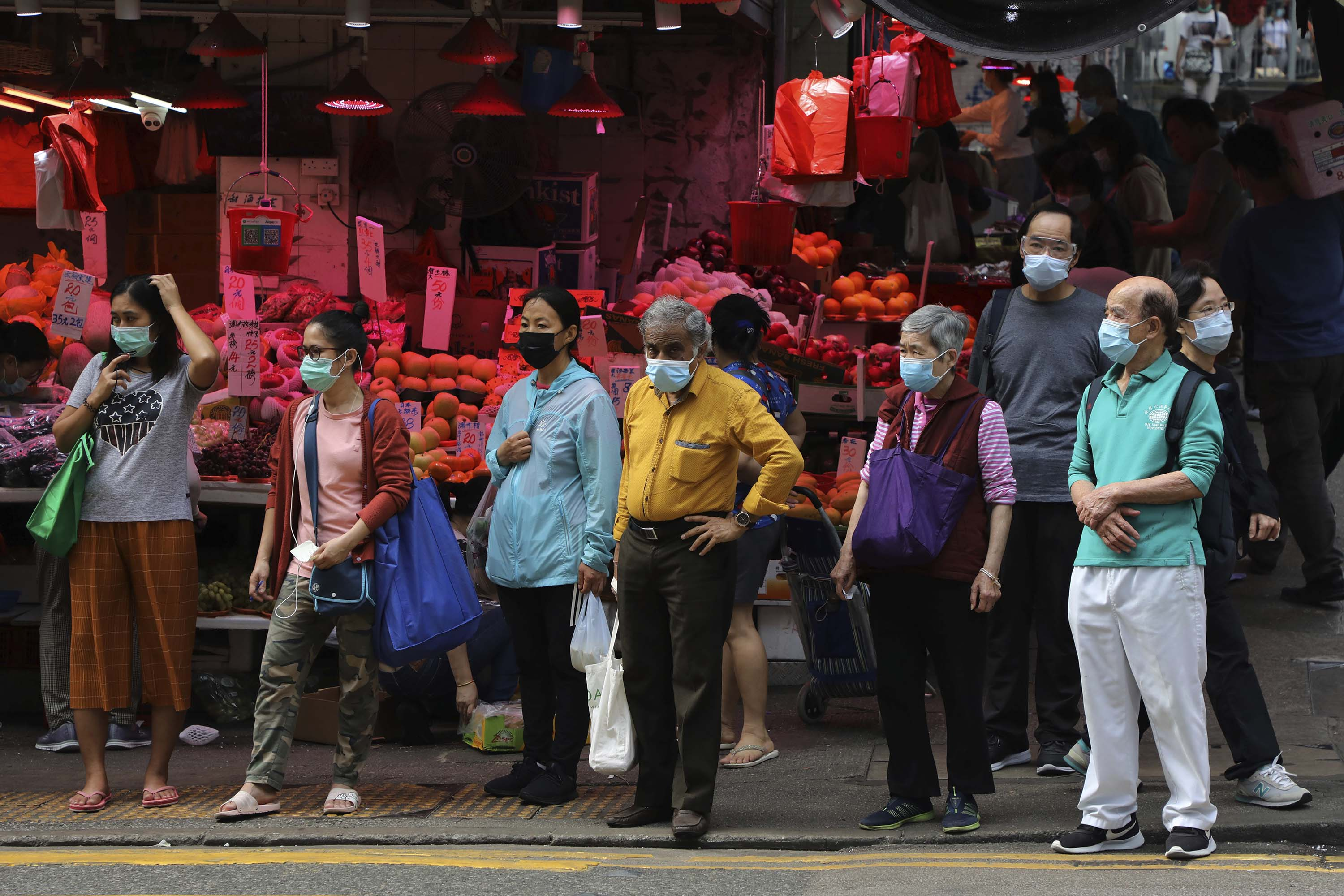 People wait to cross a street in Hong Kong on April 18.