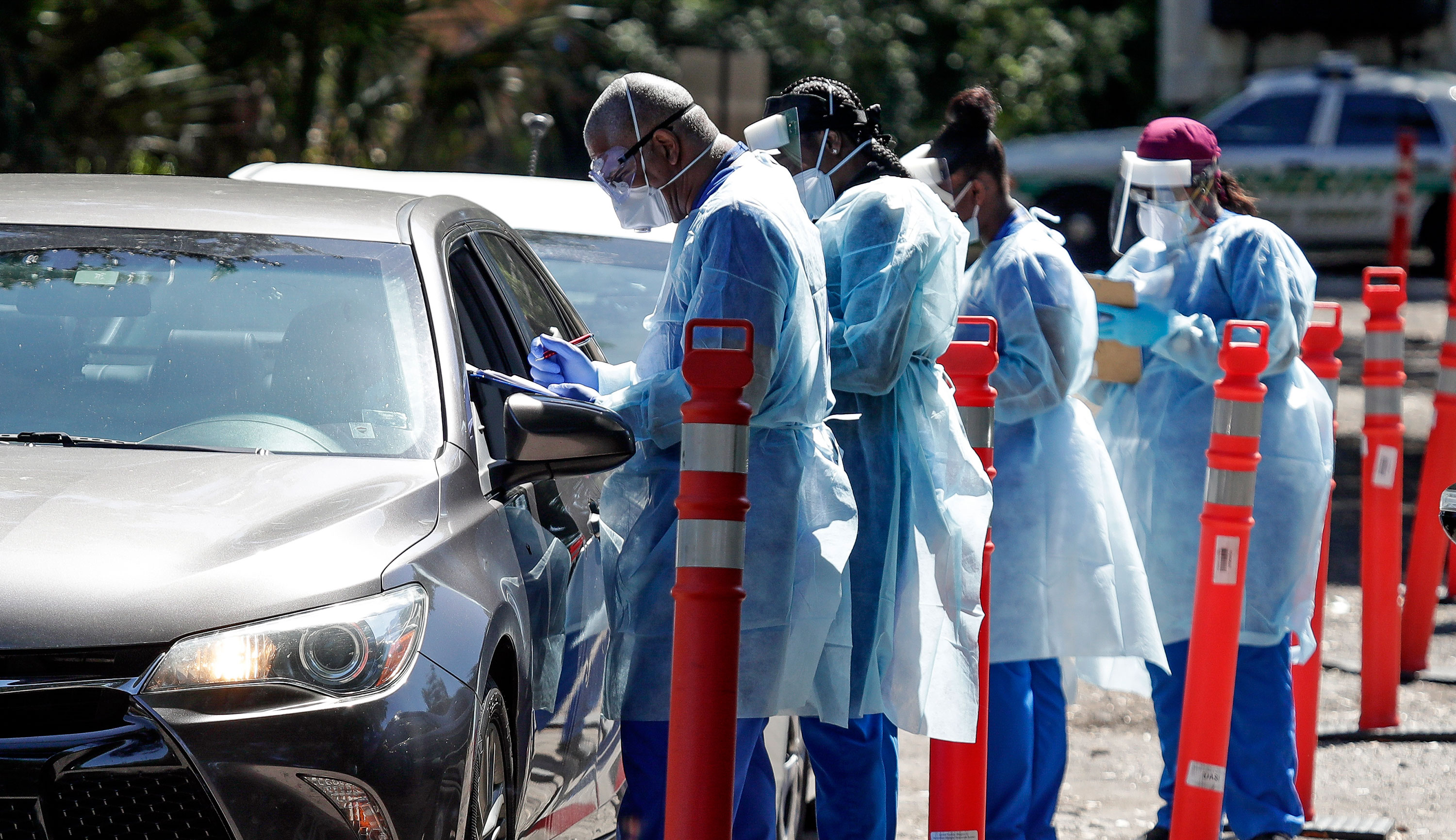 Health workers conduct Covid-19 tests at a drive-through testing site in Sanford, Florida on April 27.