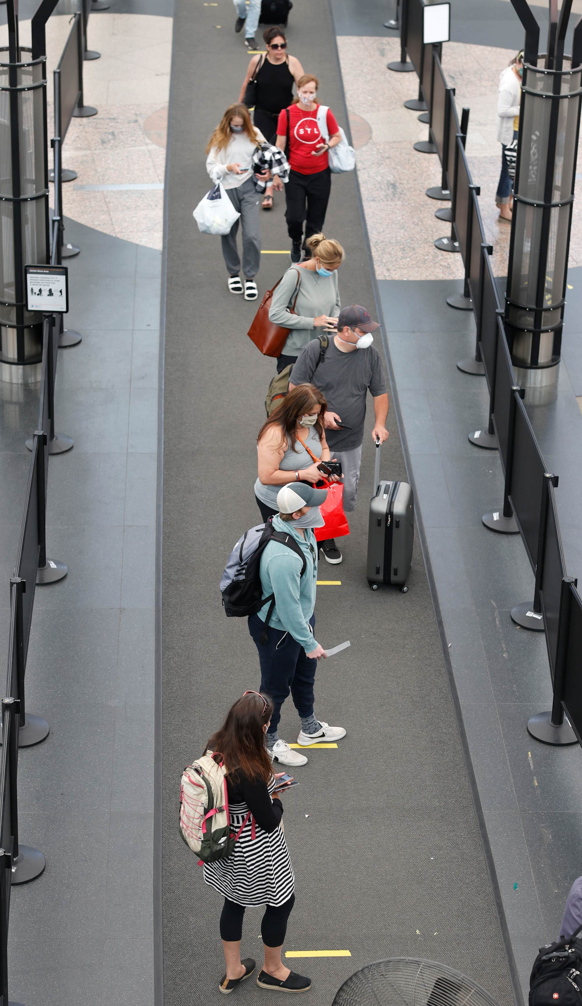 Passengers queue up in to pass through the south security checkpoint in Denver International Airport on June 10 in Denver.