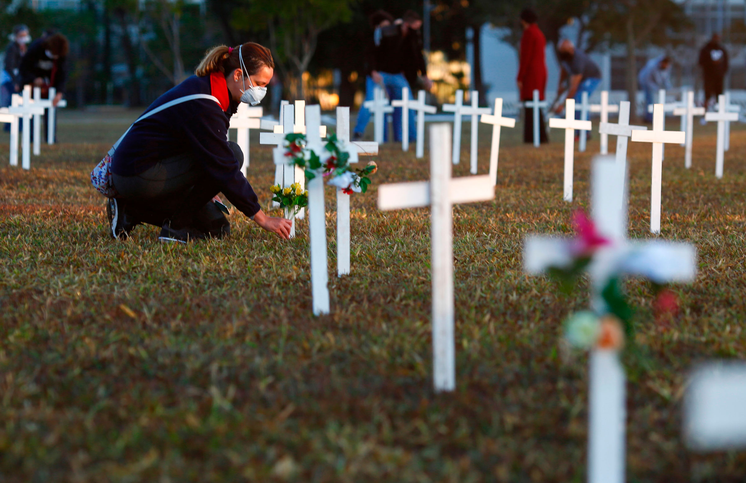 A demonstrator places flowers next to a cross during a protest in front of the National Congress in Brasilia, Brazil, on Sunday.