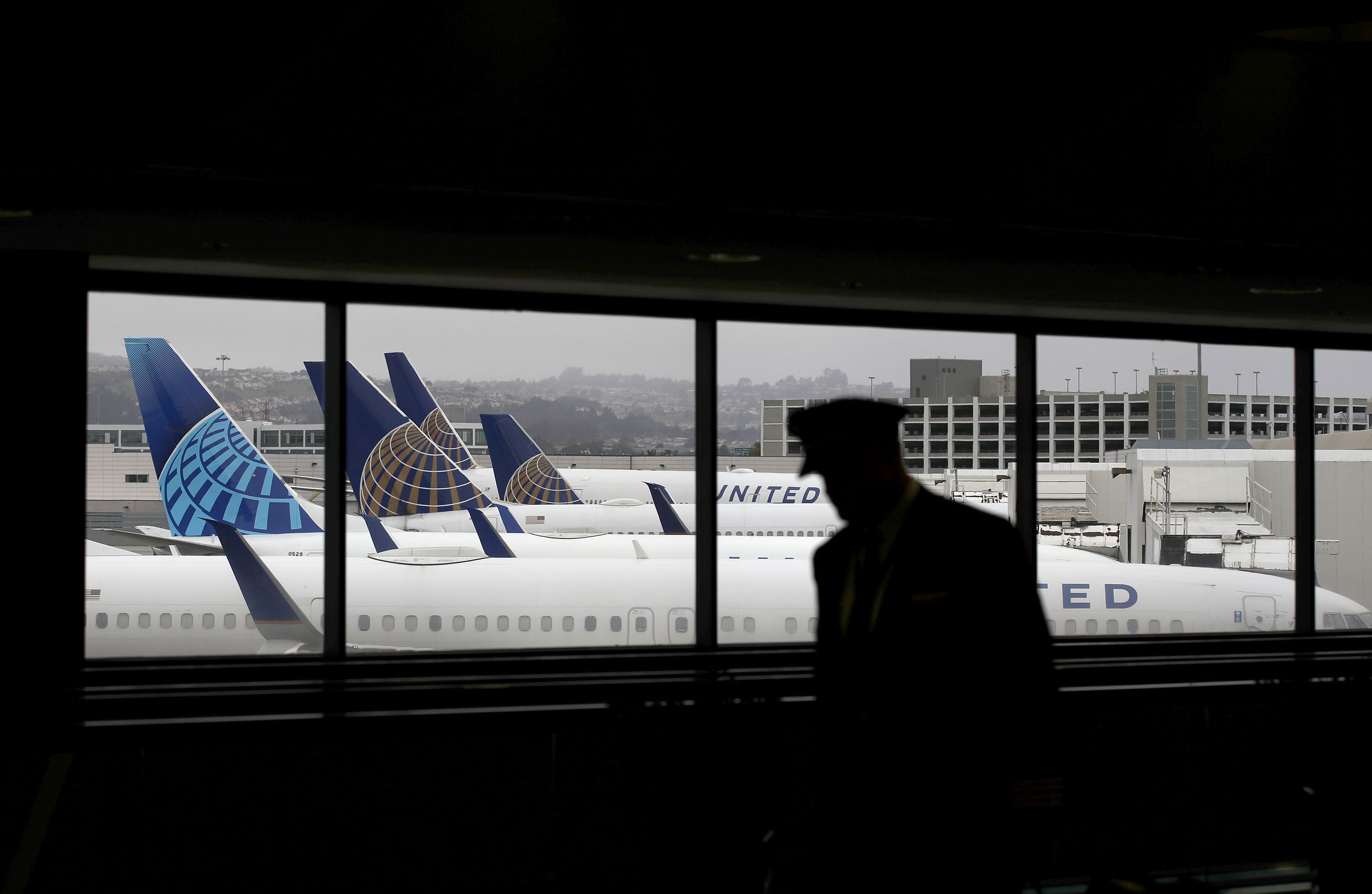 A pilot walks by United Airlines planes as they sit parked at gates at San Francisco International Airport in April 2020.