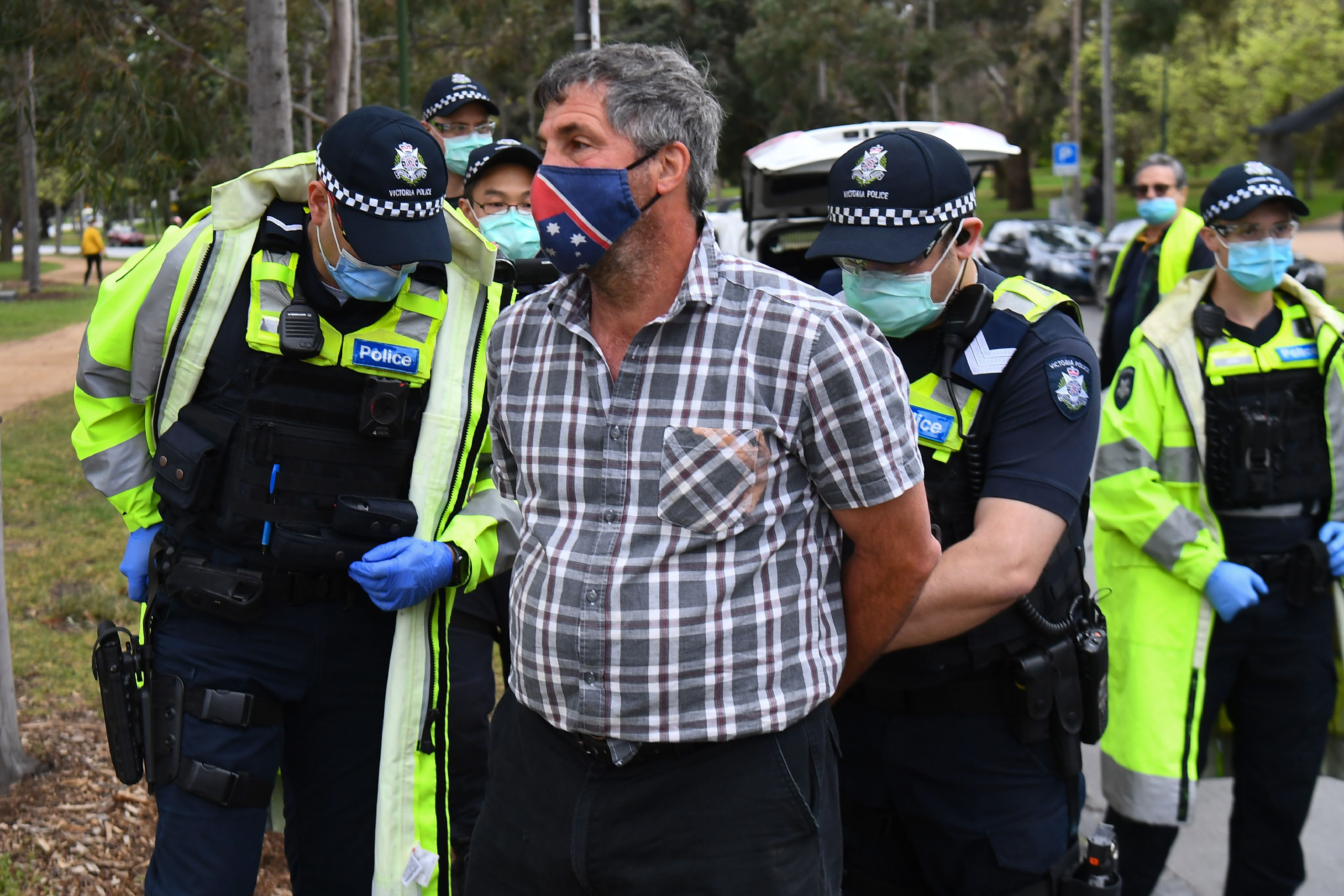 Police detain a protester during an anti-lockdown rally in Melbourne on September 12, 2020.