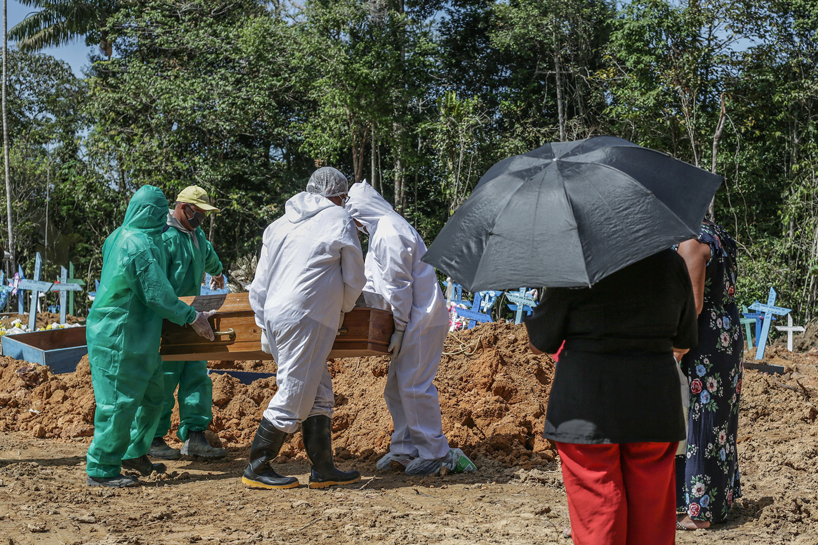 People attend a funeral for a relative who died from coronavirus in Manaus, Brazil.