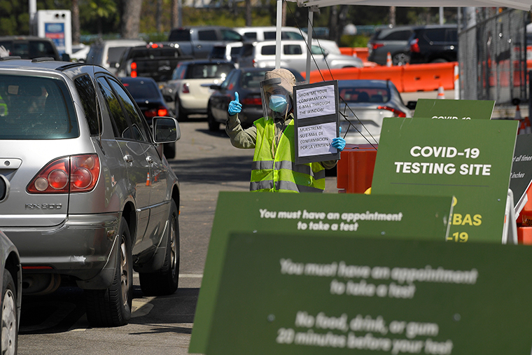 Workers direct cars as they wait in line for coronavirus testing at Dodger Stadium on Tuesday, July 14, in Los Angeles.