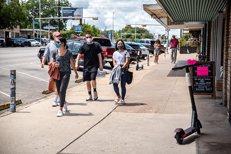 Pedestrians wear protective masks walk down a sidewalk in Austin, Texas, on Thursday, June 25.