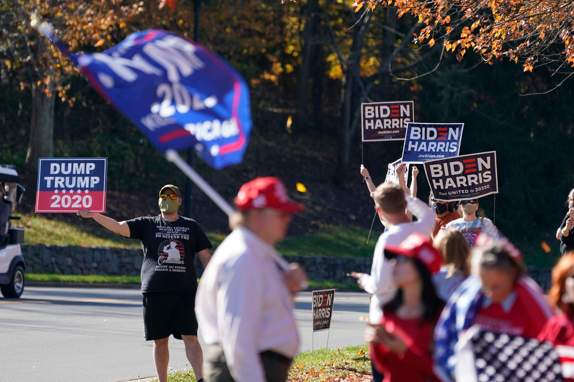 People wave signs and flags at the entrance to Trump National golf club in Sterling, Virginia, on November 7.