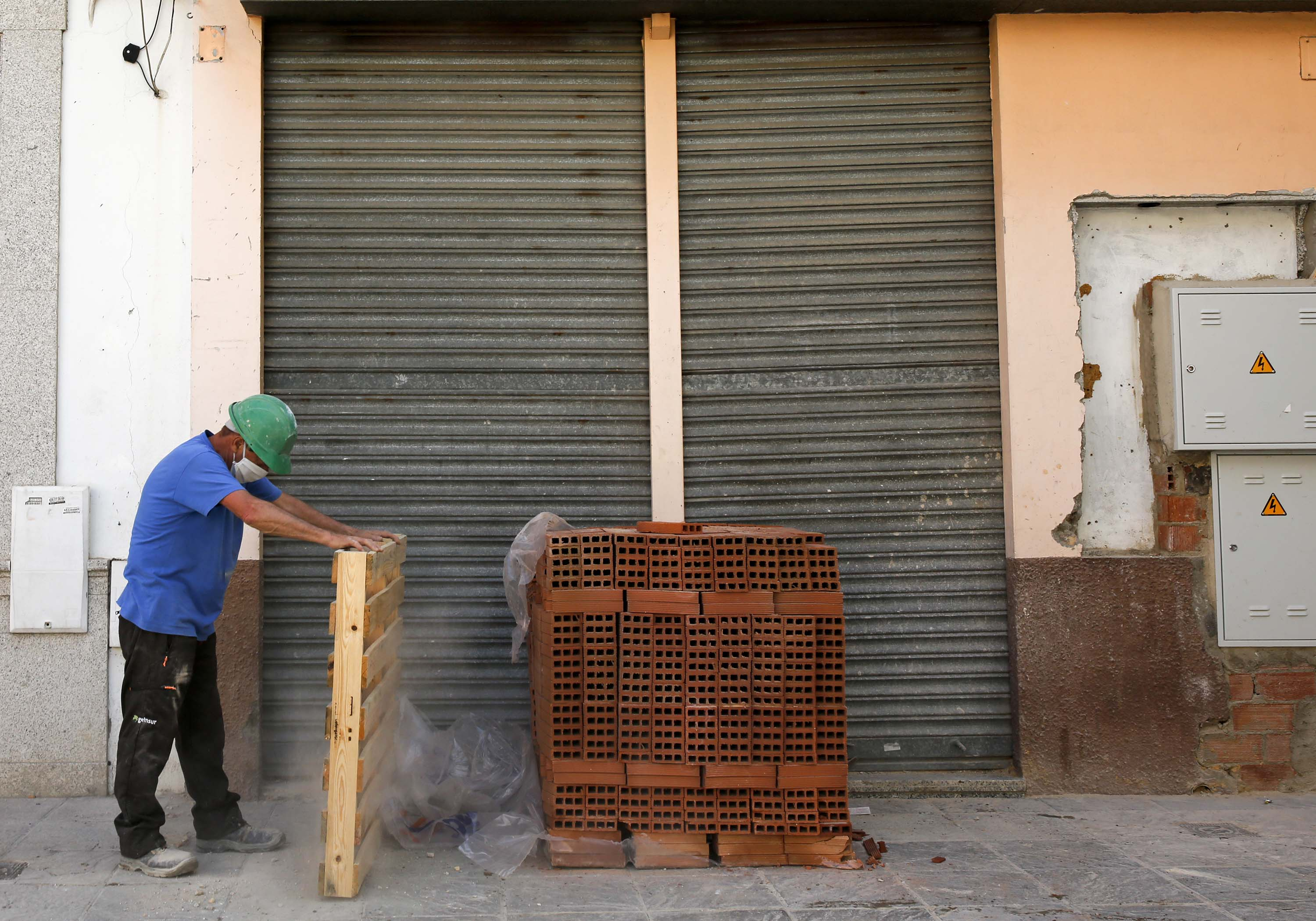A bricklayer works at a construction site in Seville, Spain on May 8.
