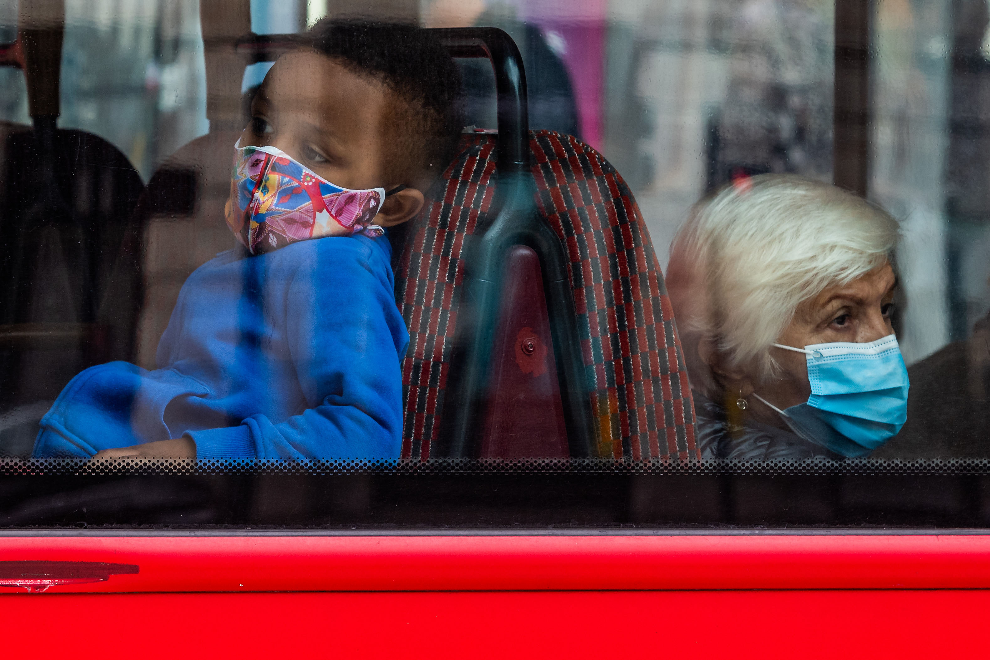 People ride a bus in London on July 28.