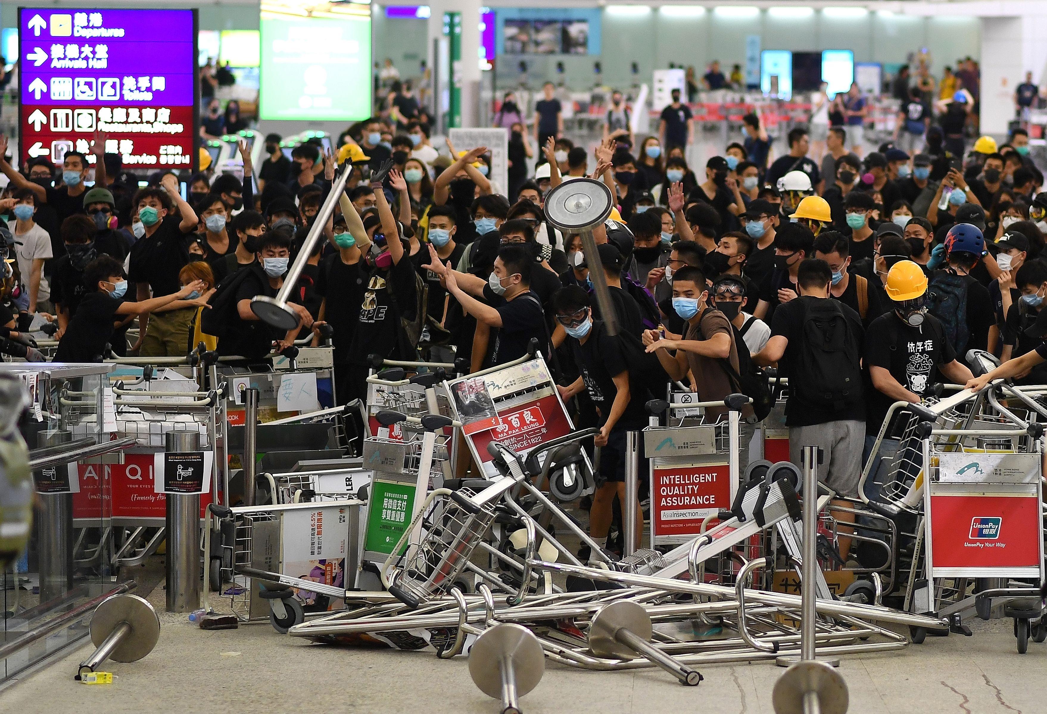 Protestors block the entrance at Hong Kong's international airport on August 13, 2019.