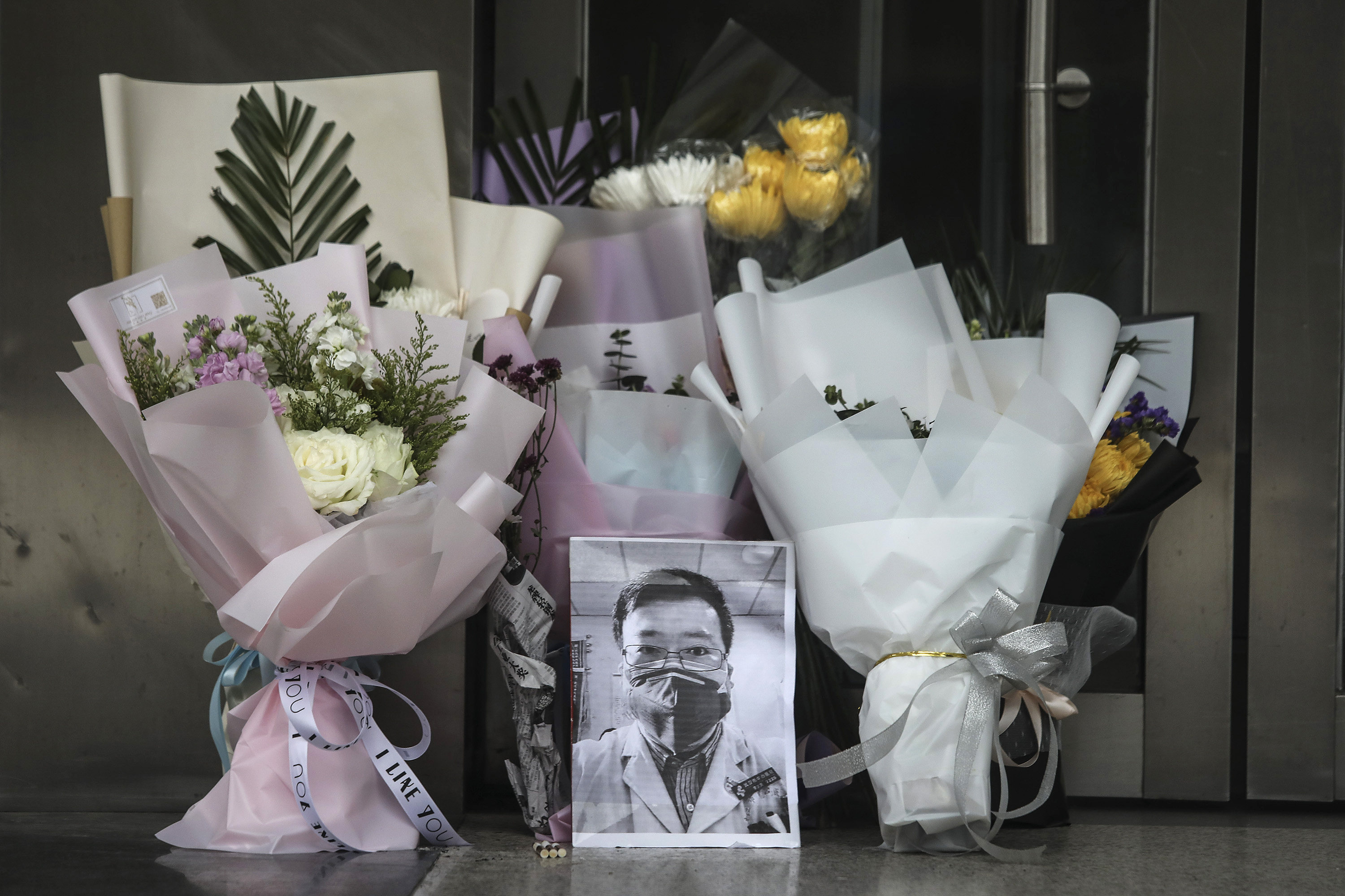 A portrait of Dr. Li Wenliang is left at Li's hospital in Wuhan on Friday.