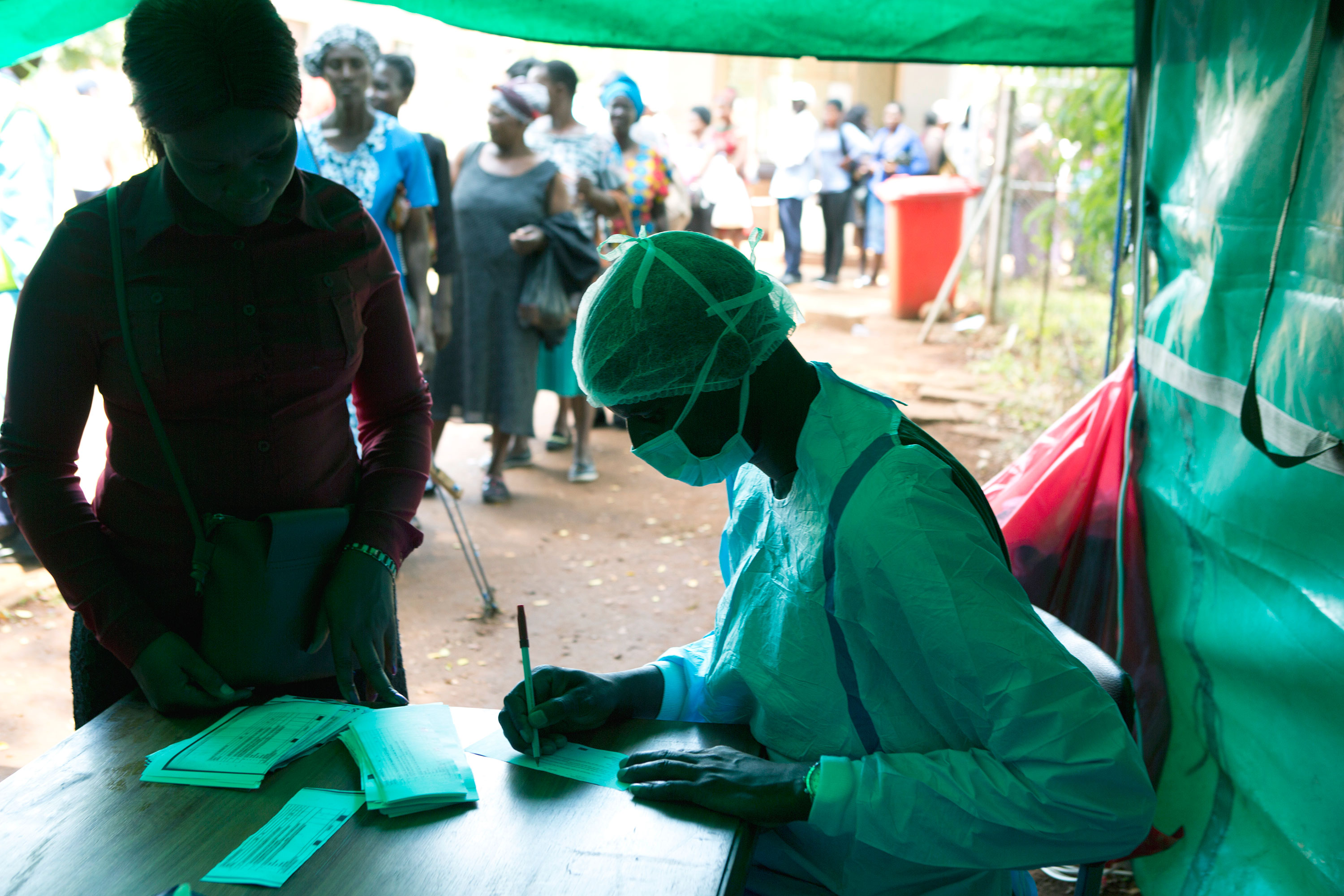 People wait in a queue to have their temperatures taken by health workers before entering a public hospital, in Harare, Zimbabwe, Saturday, March 21, 2020. (AP Photo/Tsvangirayi Mukwazhi)