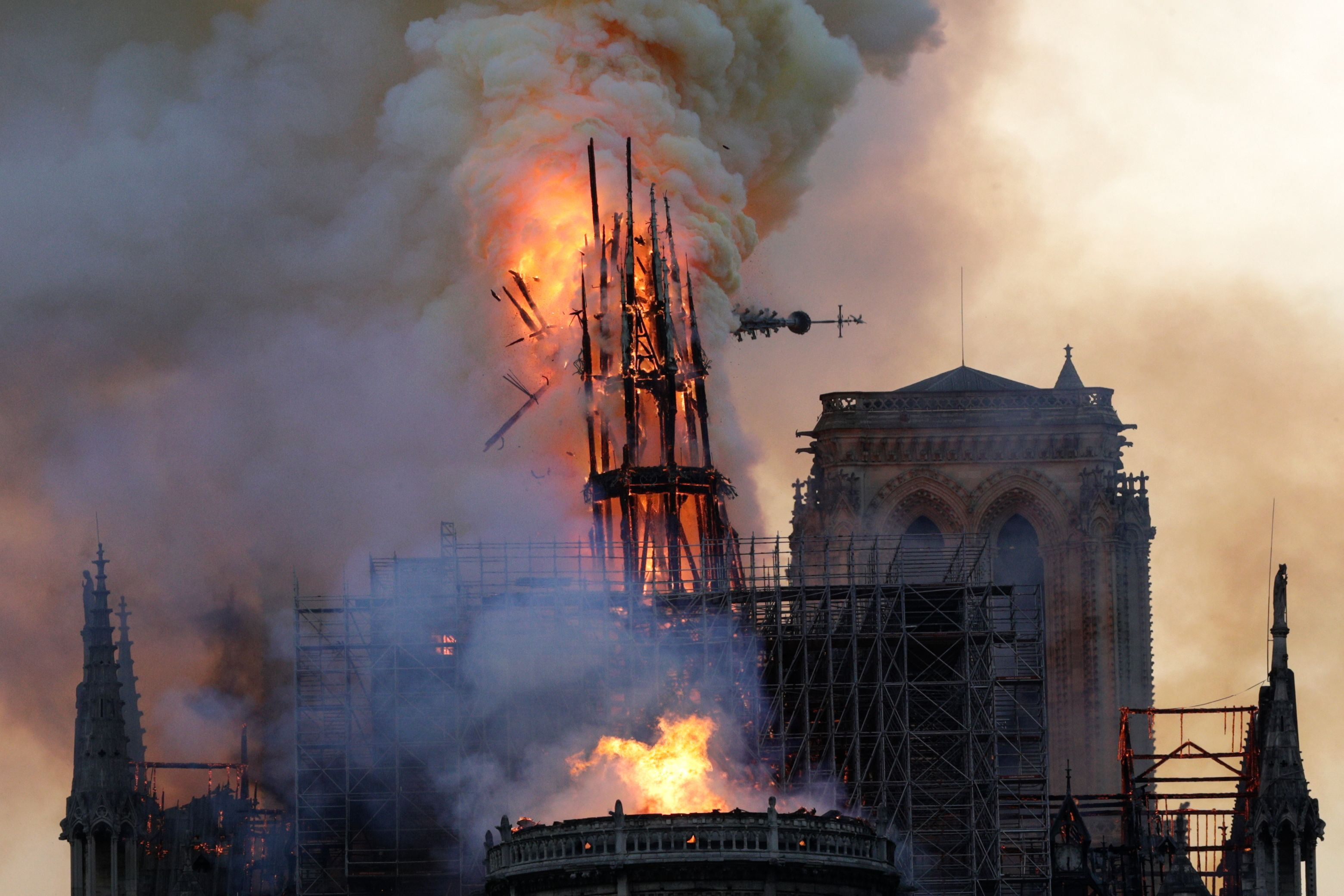 The spire collapses as smoke and flames engulf Notre Dame Cathedral in Paris.