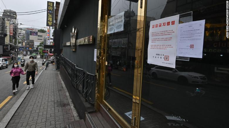 A couple wearing face masks walk past a closed nightclub in the popular nightlife district of Itaewon in Seoul on May 10.