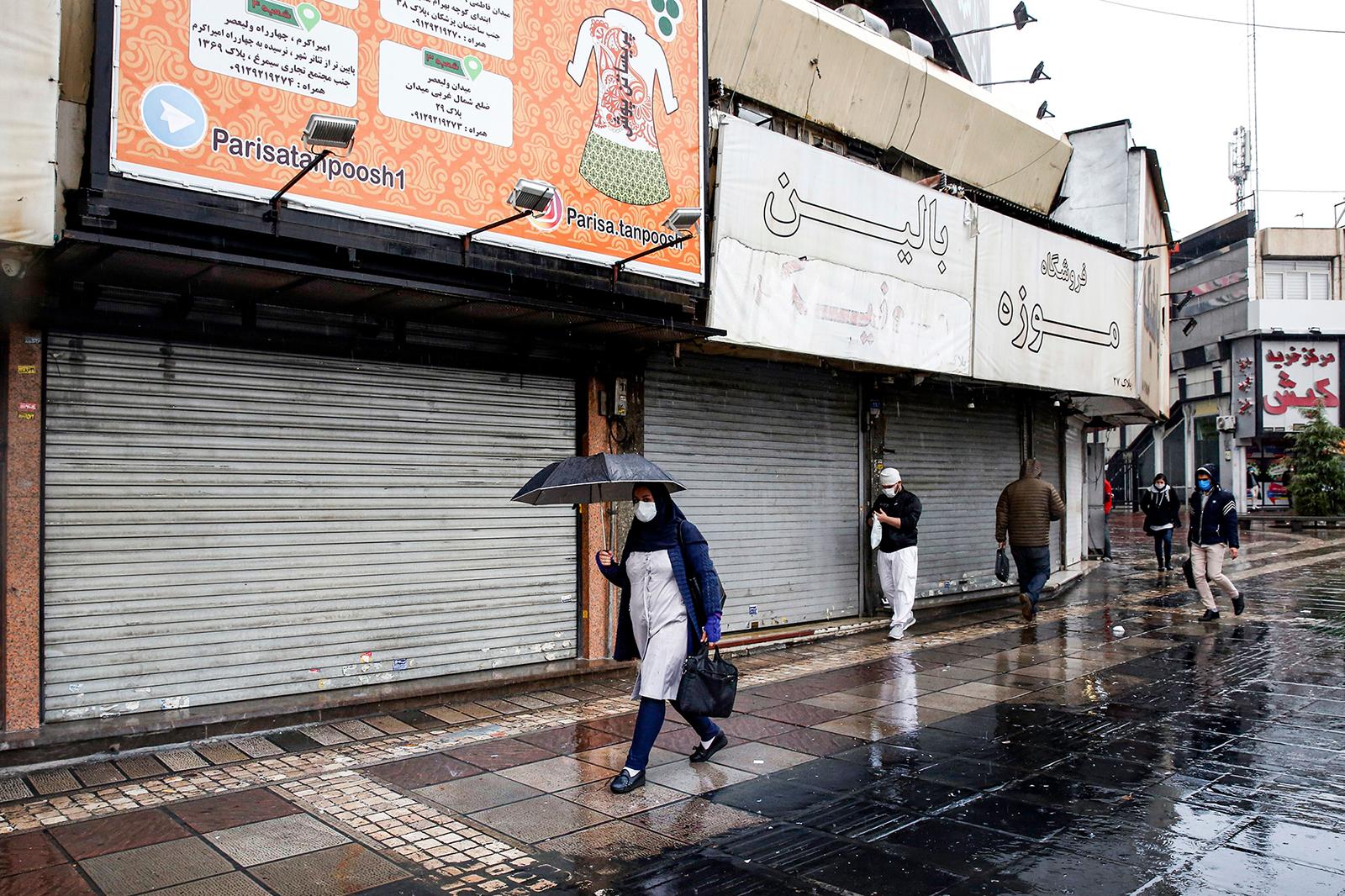 Pedestrians walk past closed shops along a street in Iran's capital Tehran on Nov. 21.