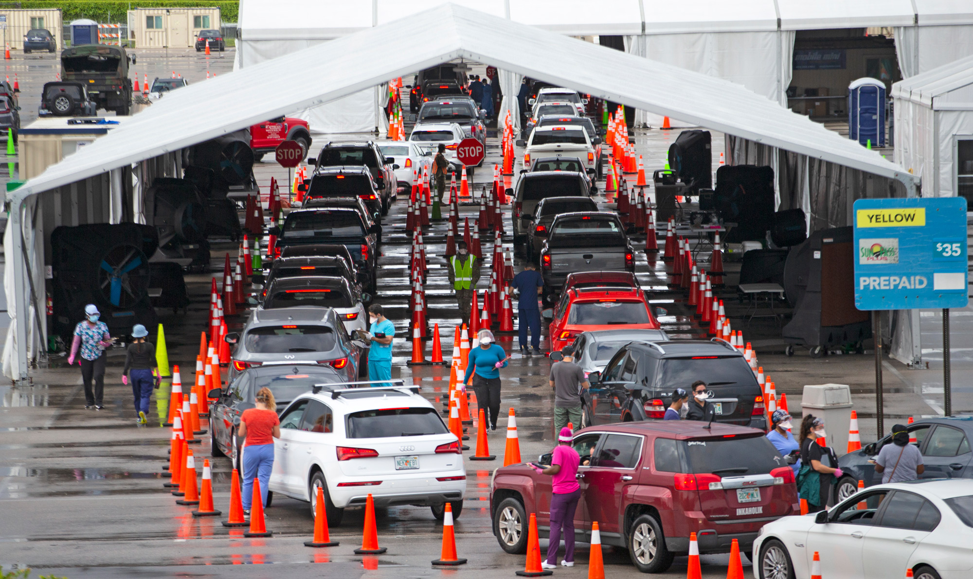 Vehicles line up as healthcare workers help to check-in people being tested at the COVID-19 drive-thru testing center at Hard Rock Stadium in Miami Gardens, Florida, on November 22.