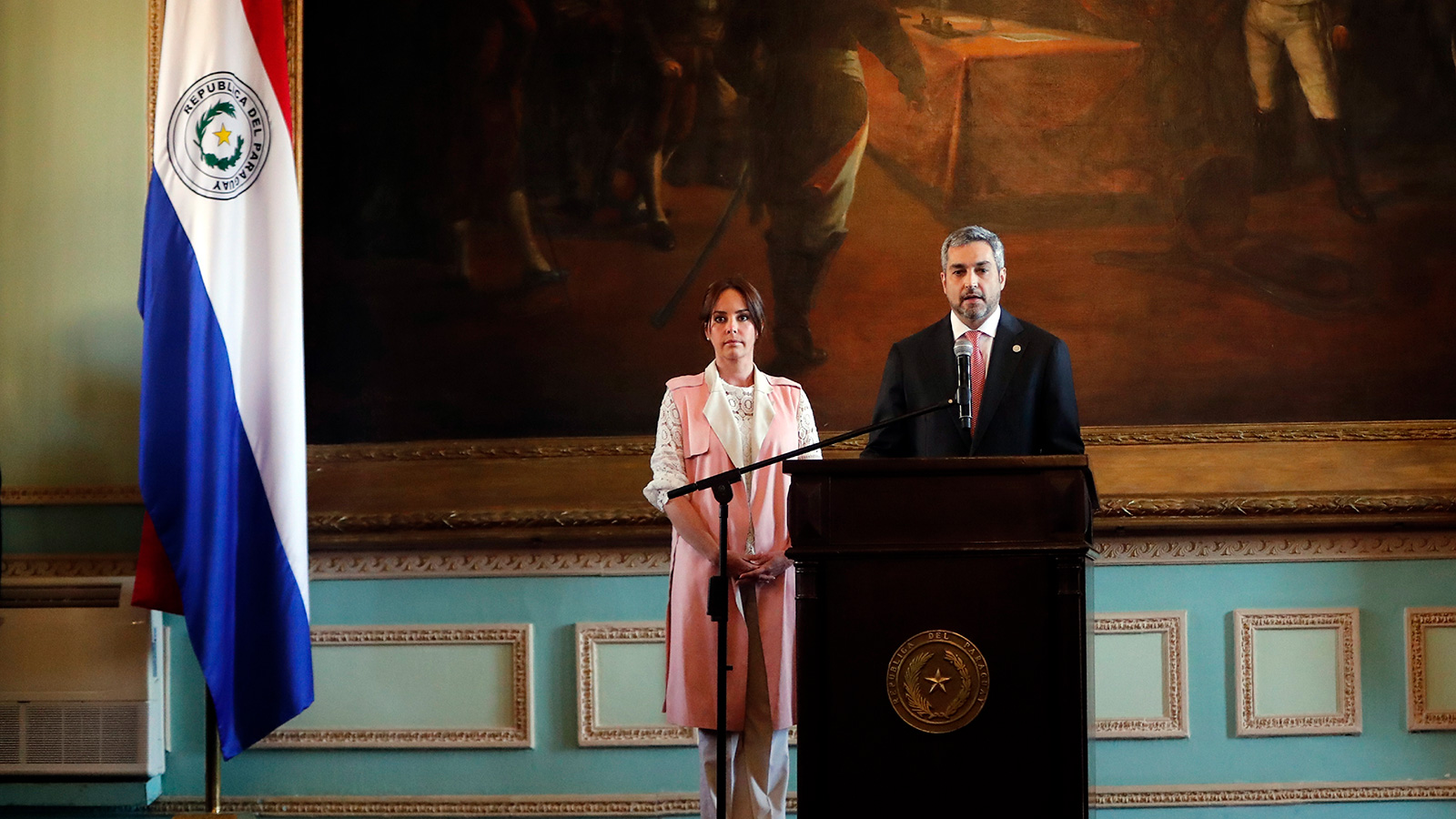 In this August 1, 2019 file photo, Paraguay's First Lady Silvana López Moreira stands next to her husband President Mario Abdo Benitez as he speaks to the nation from the Palacio de Lopez in Asuncion, Paraguay.