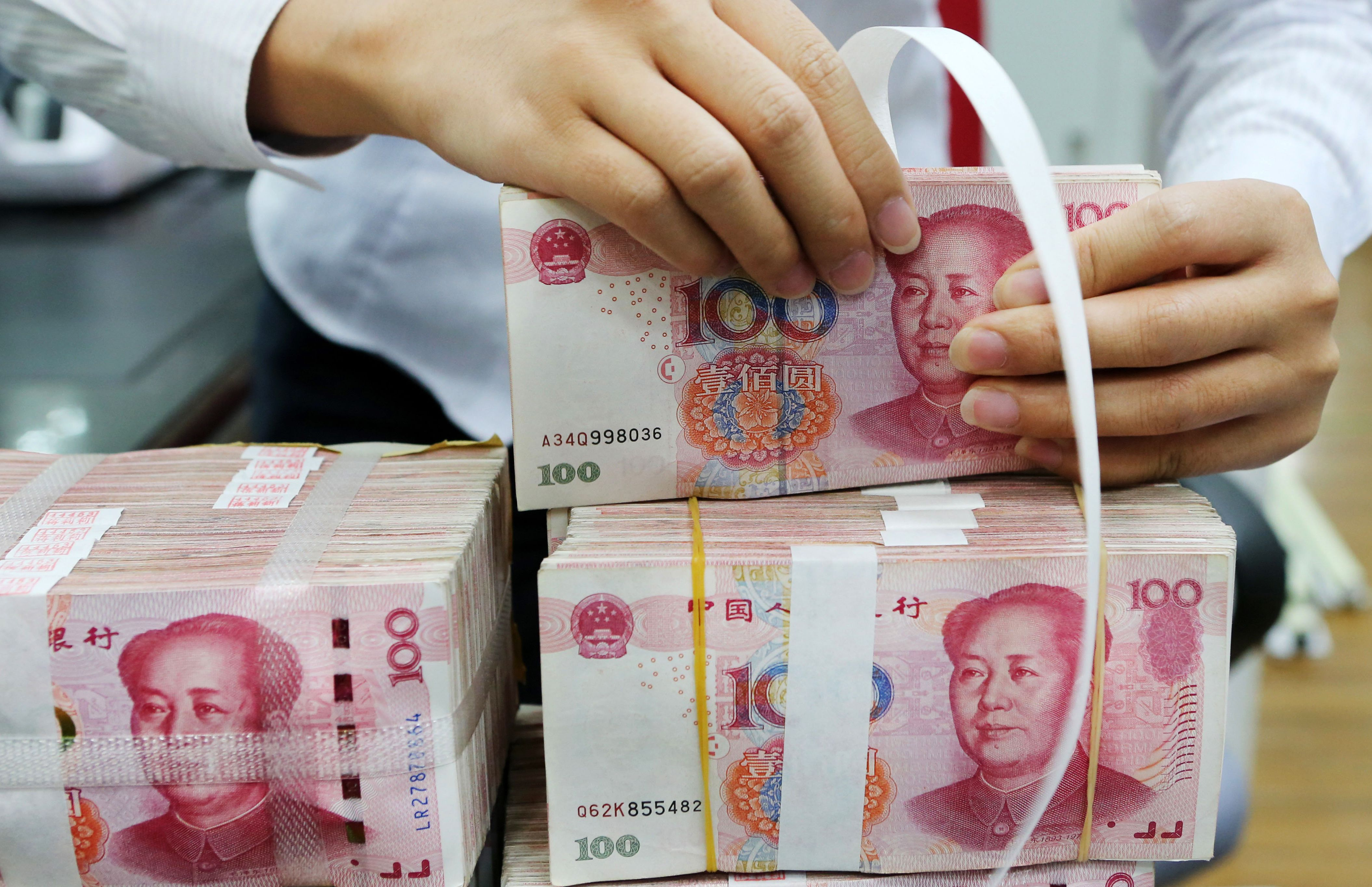 An employee packages 100-yuan notes at a bank in Nantong in China's eastern Jiangsu province on July 23, 2018.