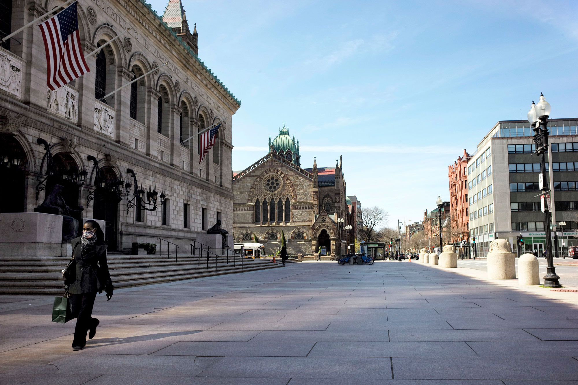 A person wearing a mask out of concern for the coronavirus walks past the Boston Public Library on April 29.
