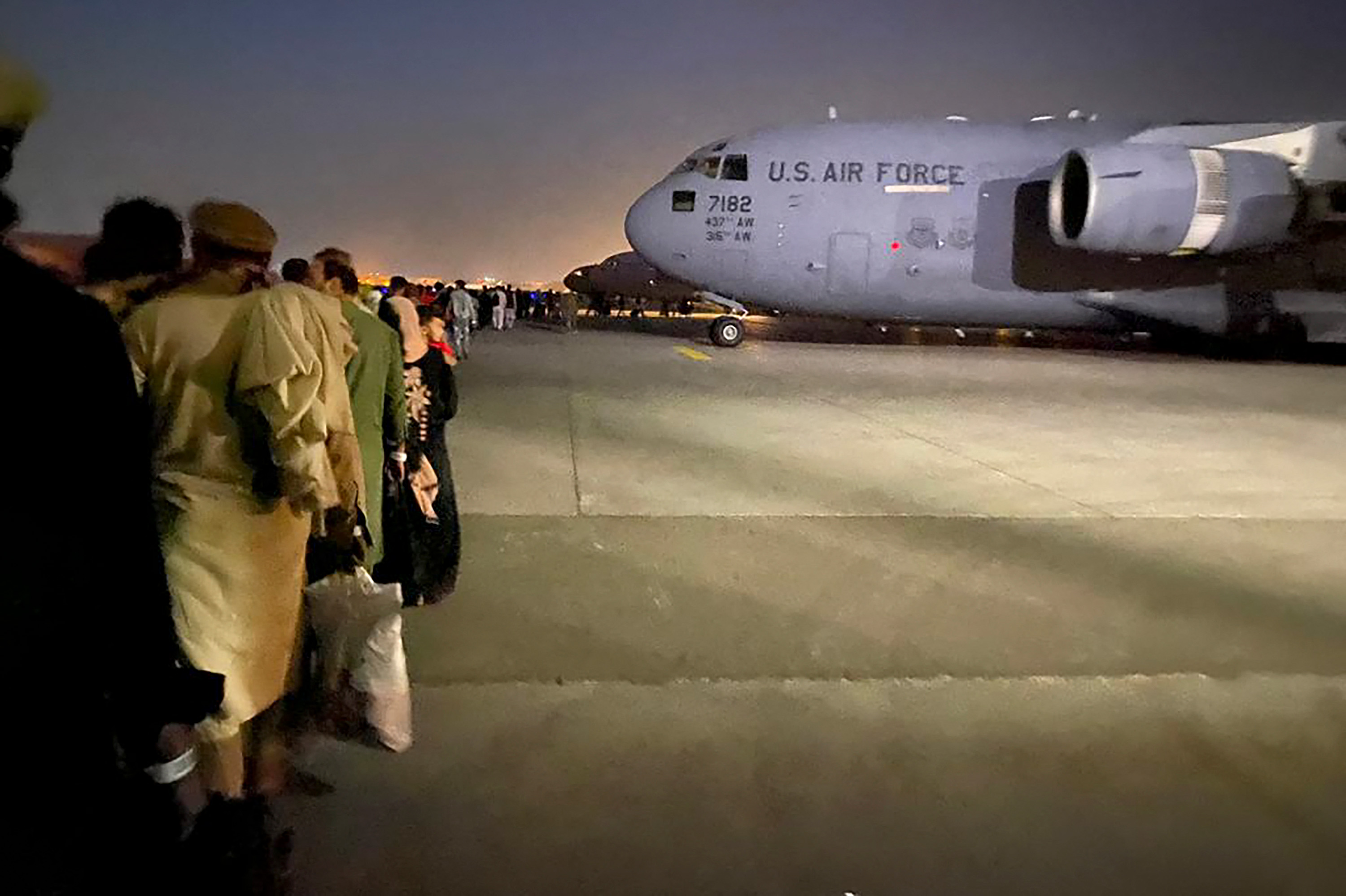 People queue up to board a US military aircraft to leave Afghanistan at the military airport in Kabul on August 19.