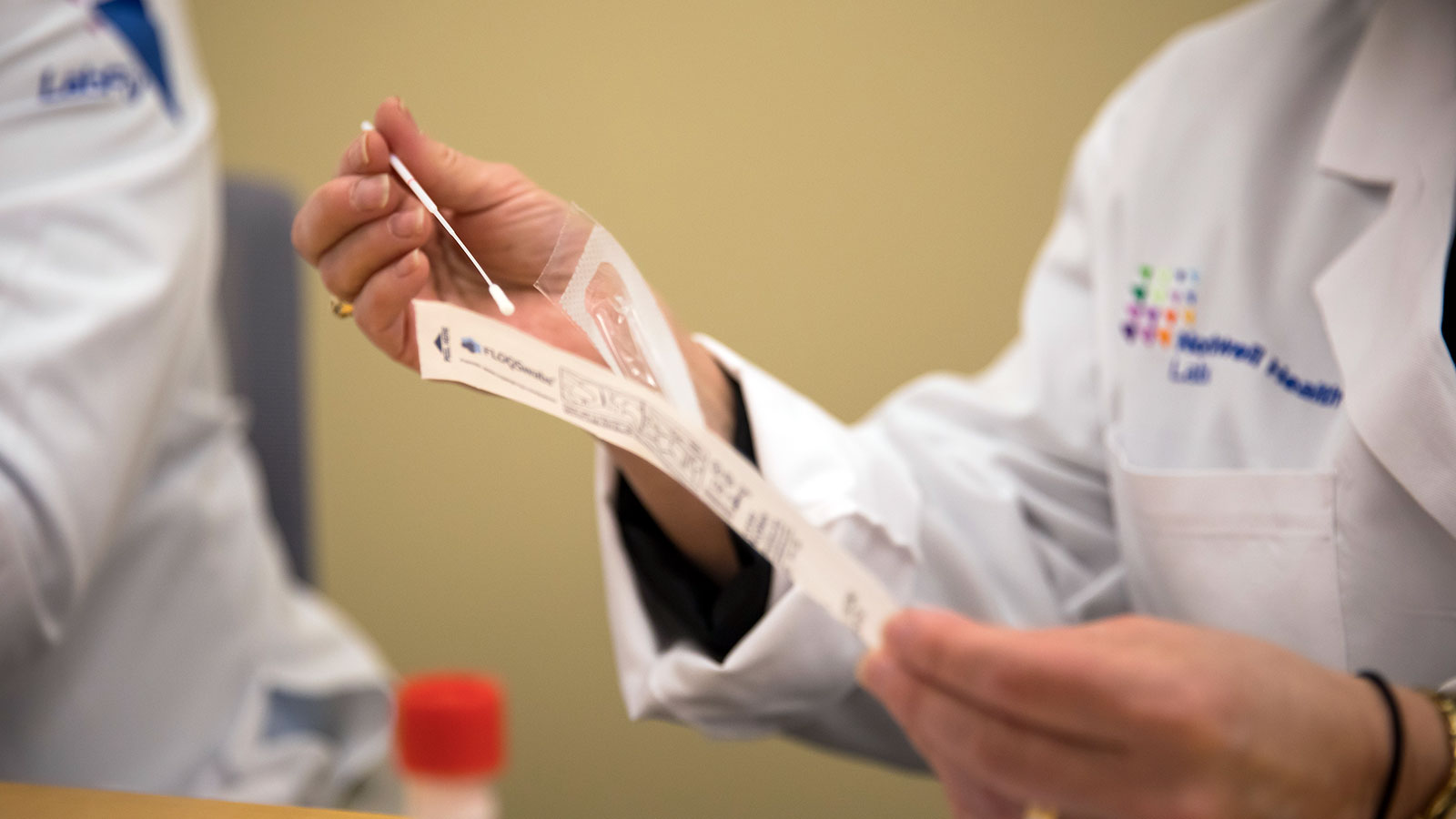 A pathologist holds a nasal swab from a Covid-19 test kit.