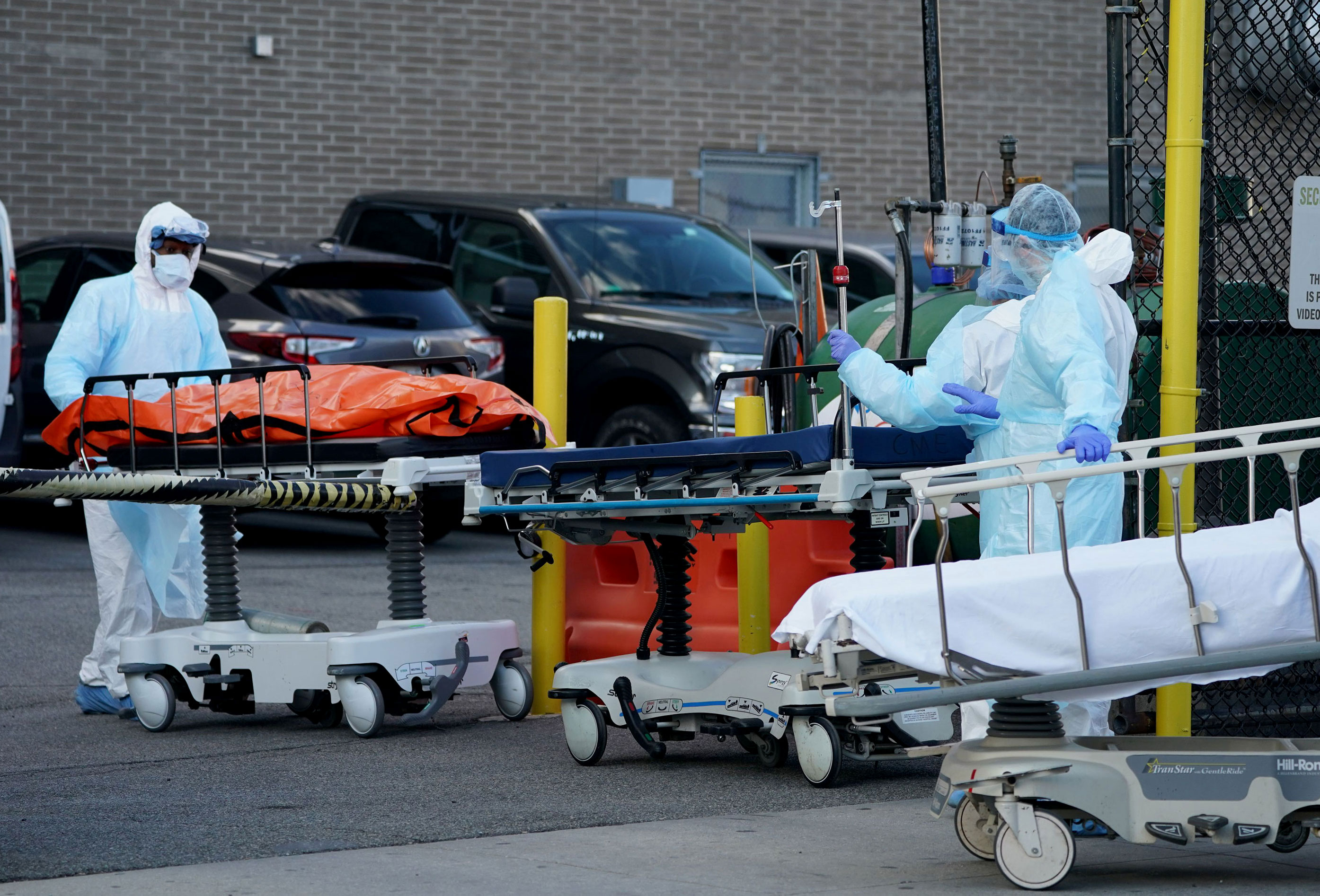 Bodies are moved to a refrigerator truck serving as a temporary morgue outside of Wyckoff Hospital in Brooklyn, New York on April 4.