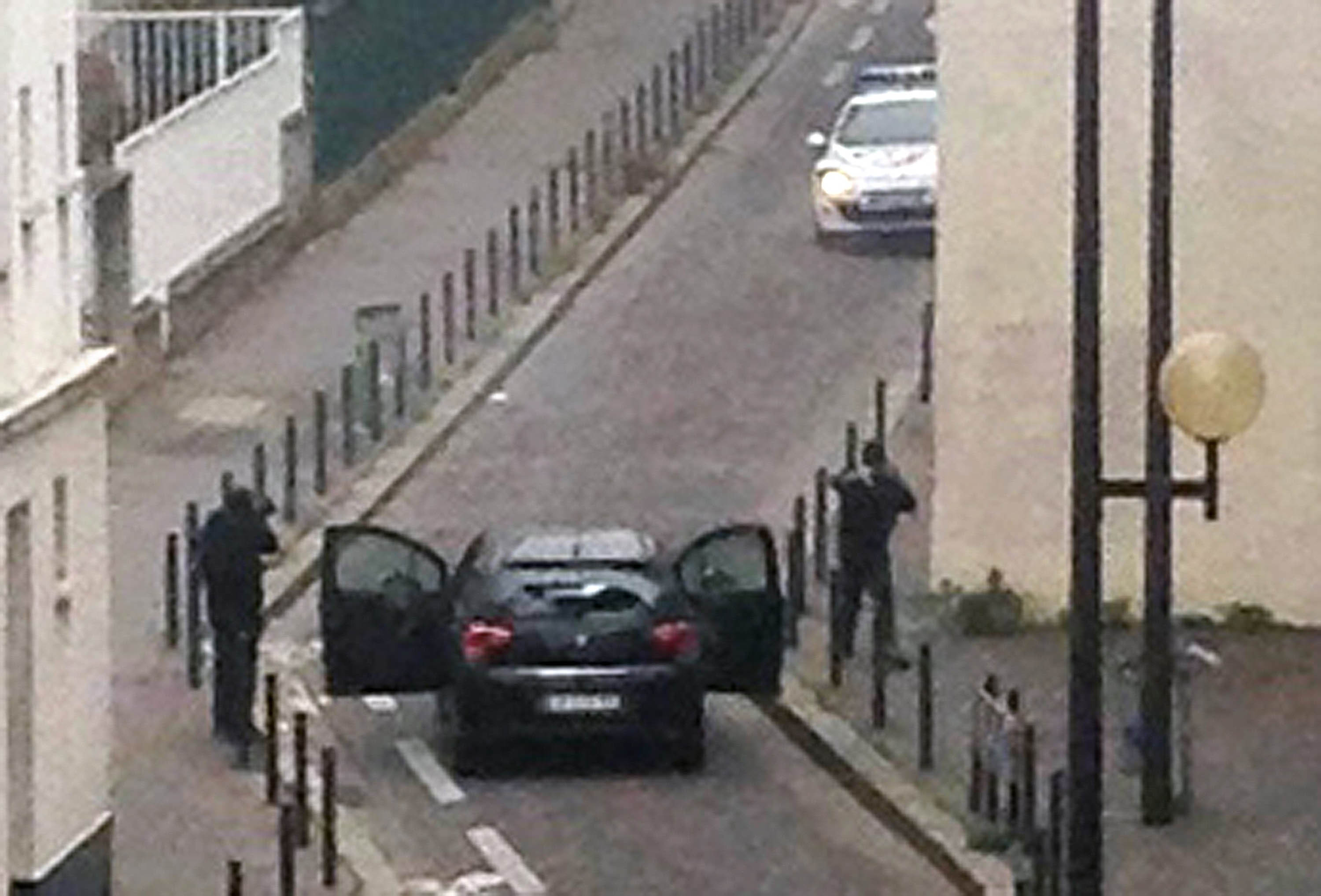 Armed gunmen face police officers near the offices of the French satirical newspaper Charlie Hebdo during the attack in Paris, on January 7, 2015.