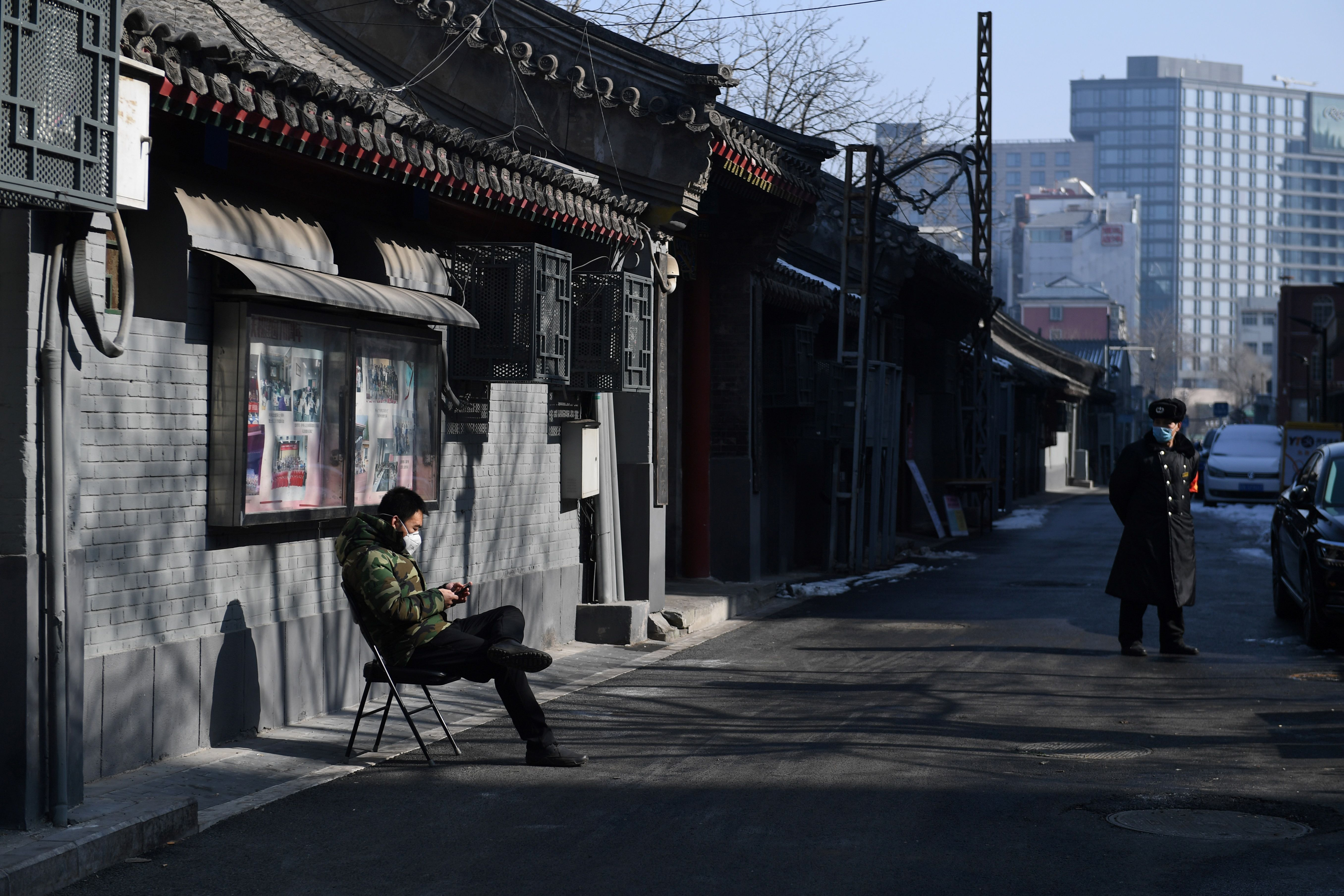A man monitors traffic in an alley in central Beijing on February 10, 2020.