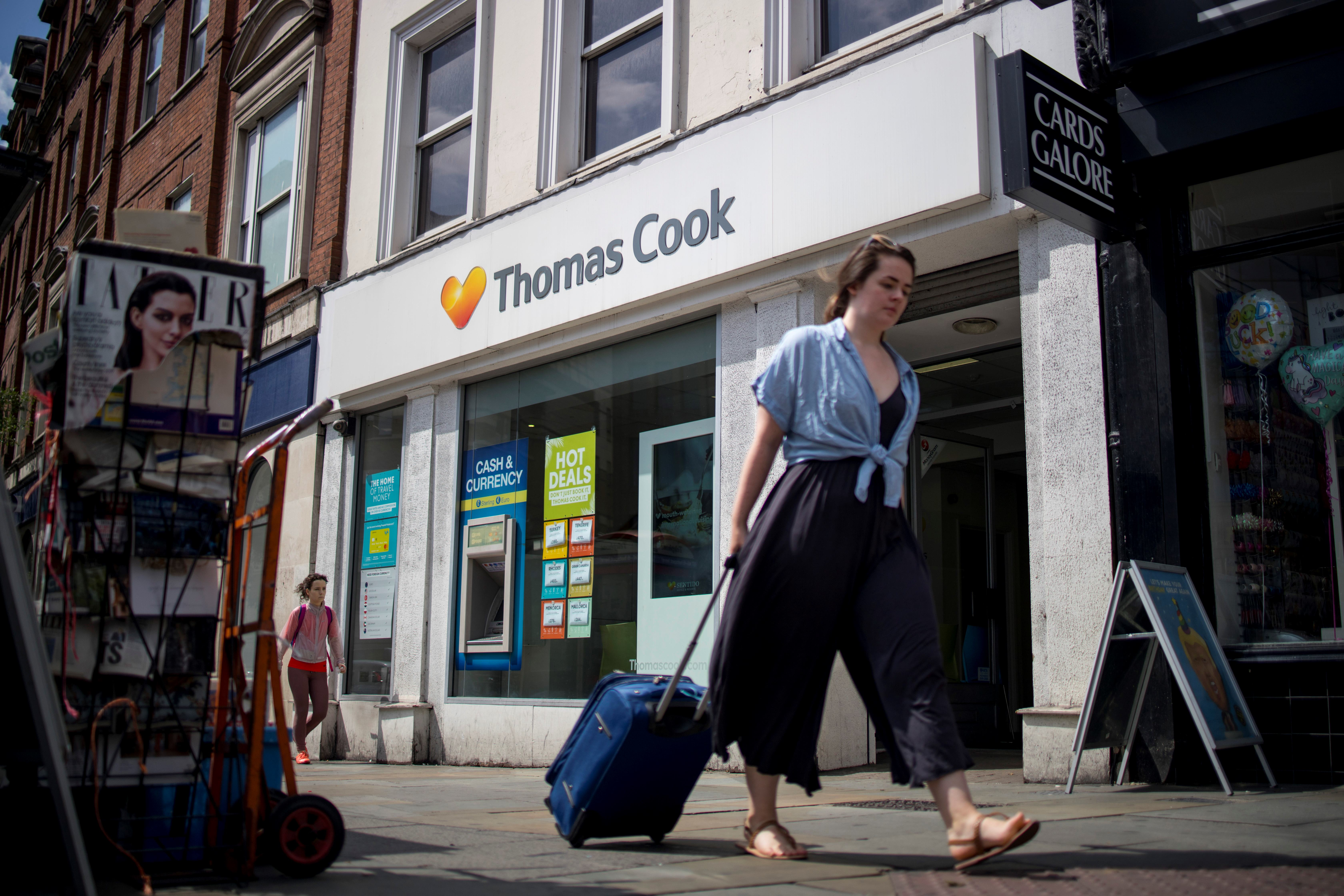 Pedestrians walk past a branch of a Thomas Cook travel agent's shop in London on July 12, 2019.