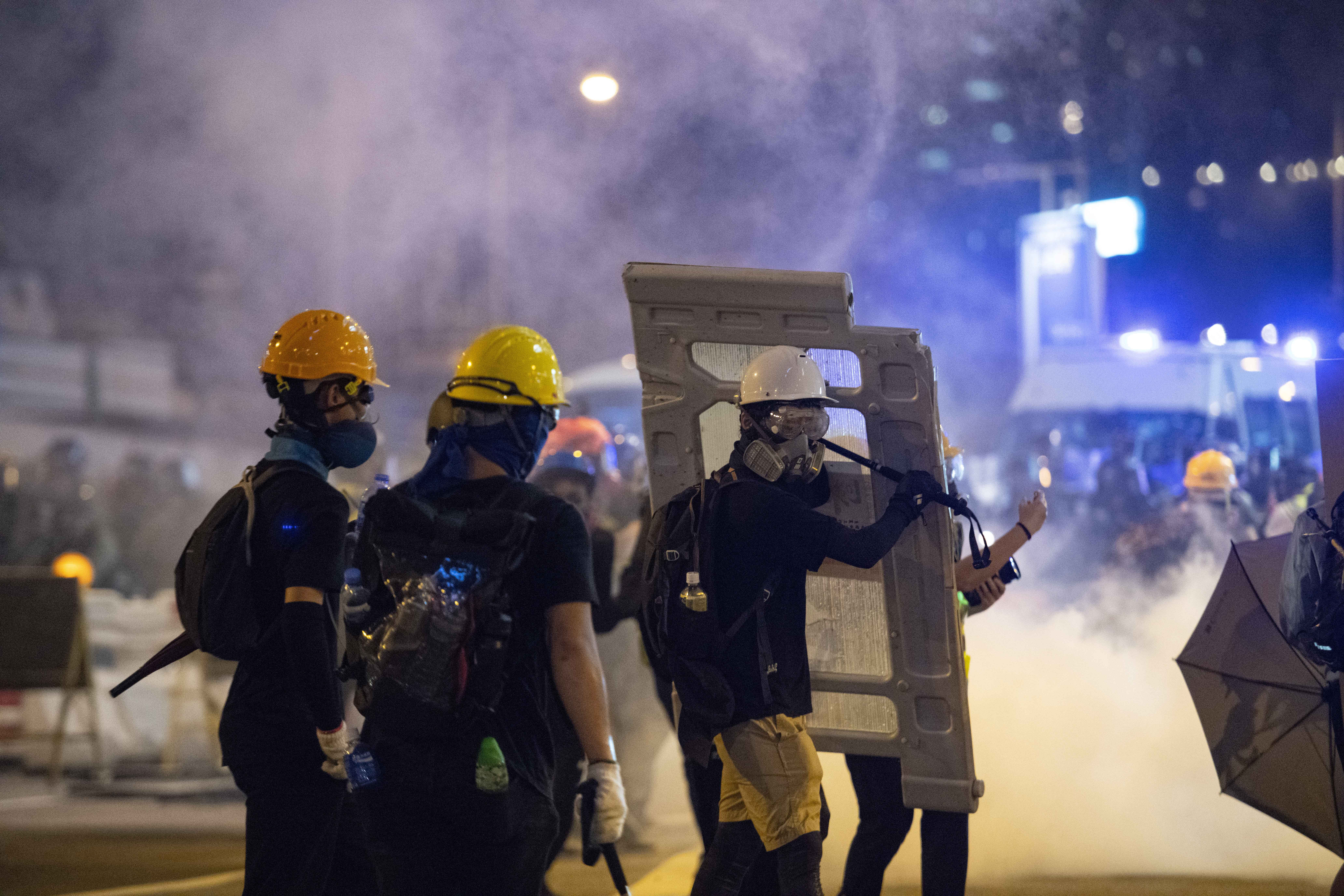 Protesters take cover amid a barrage of tear gas fire.