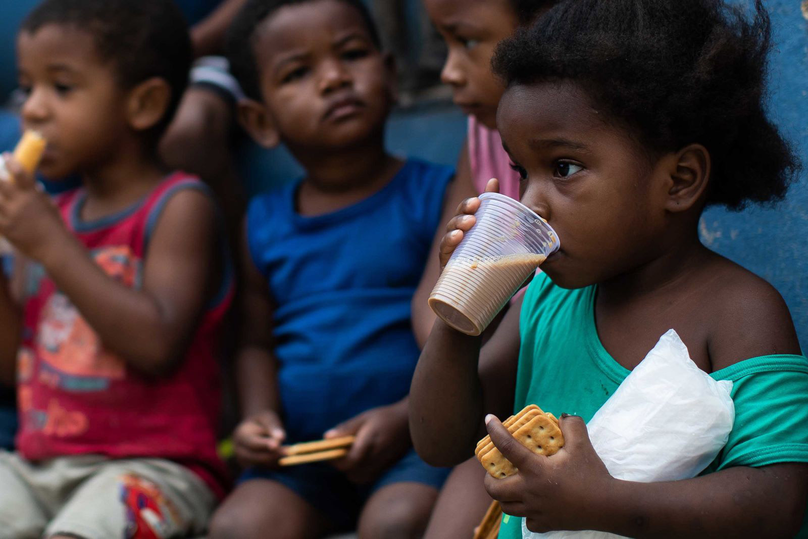 Children eat breakfast during food distribution in Rio de Janeiro, Brazil, on May 24.