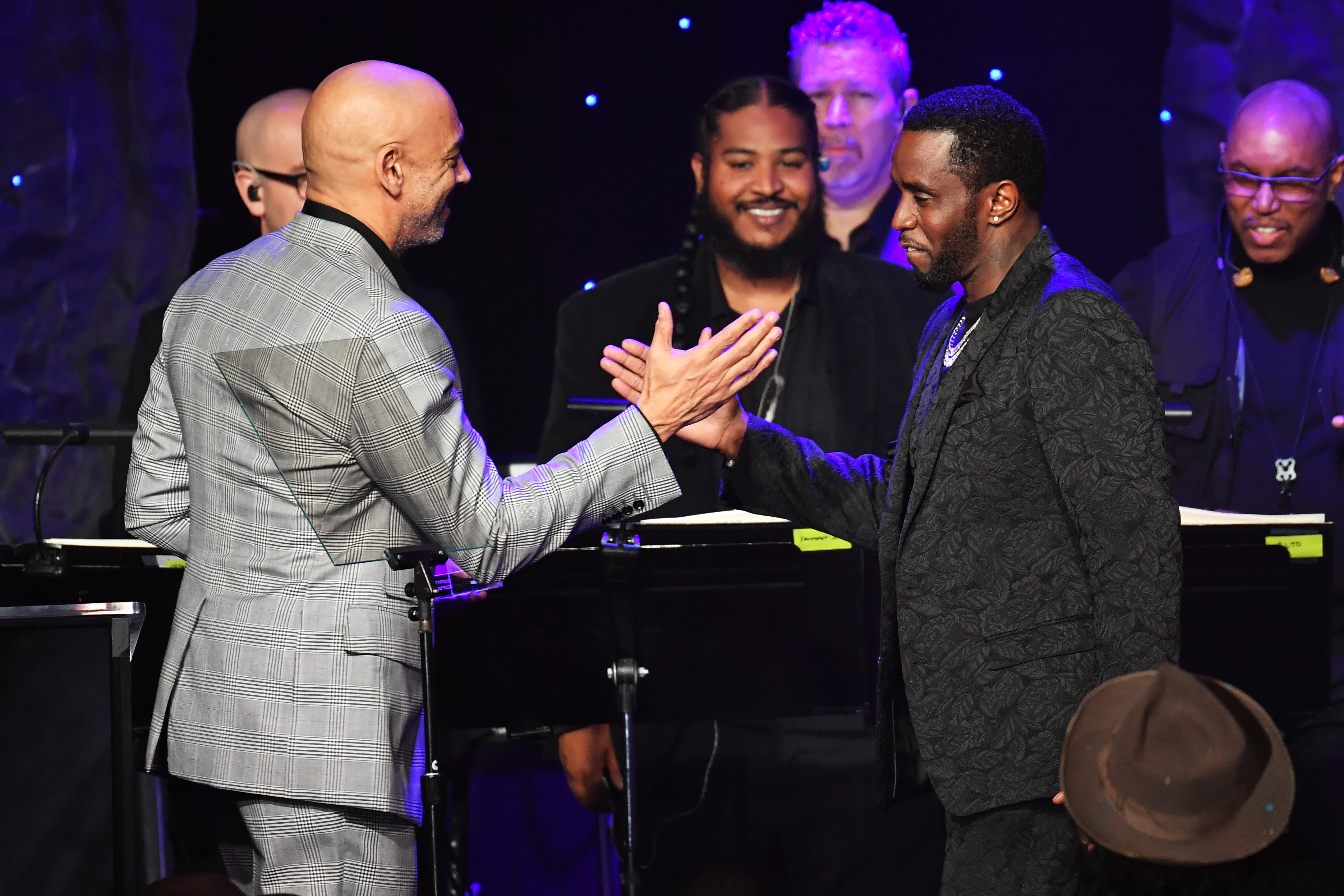 """Chair of the Board of Trustees of the Recording Academy Harvey Mason Jr. presents the President's Merit Award to honoree Sean """"Diddy"""" Combs onstage during a pre-Grammy event Sunday in Beverly Hills."""