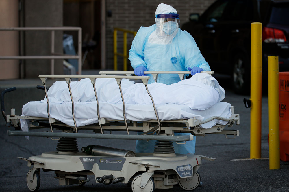 A medical worker wearing personal protective equipment wheels a body to a refrigerated trailer serving as a makeshift morgue at Wyckoff Heights Medical Center on Monday, April 6, in the Brooklyn borough of New York.