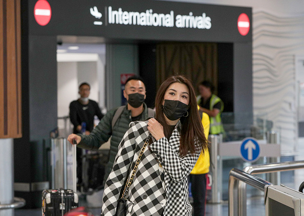 Passengers wear protective masks as they arrive at Auckland airport in New Zealand on January 29, 2020.
